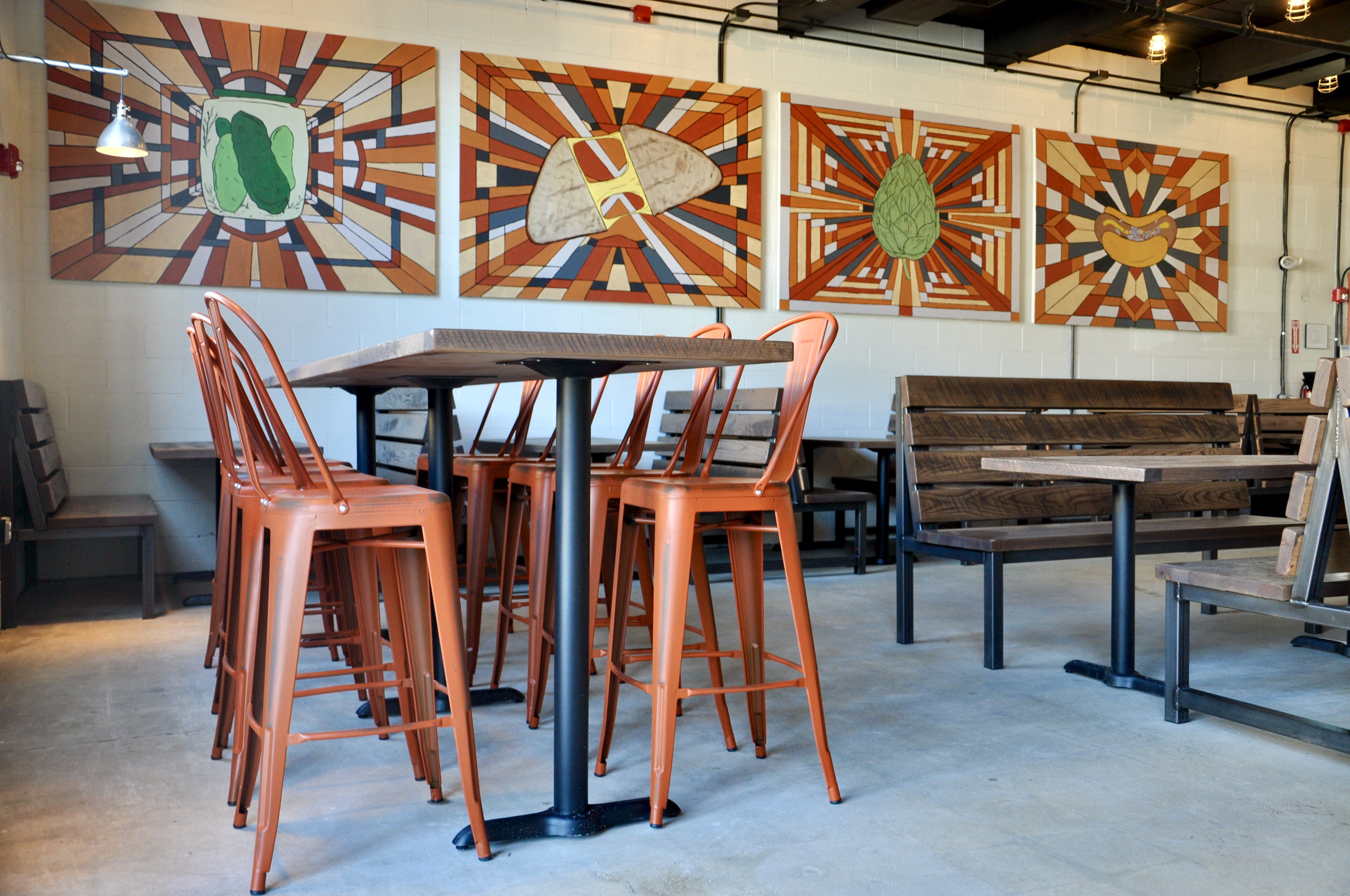 Four paintings overhang wooden booth seating inside a beer hall