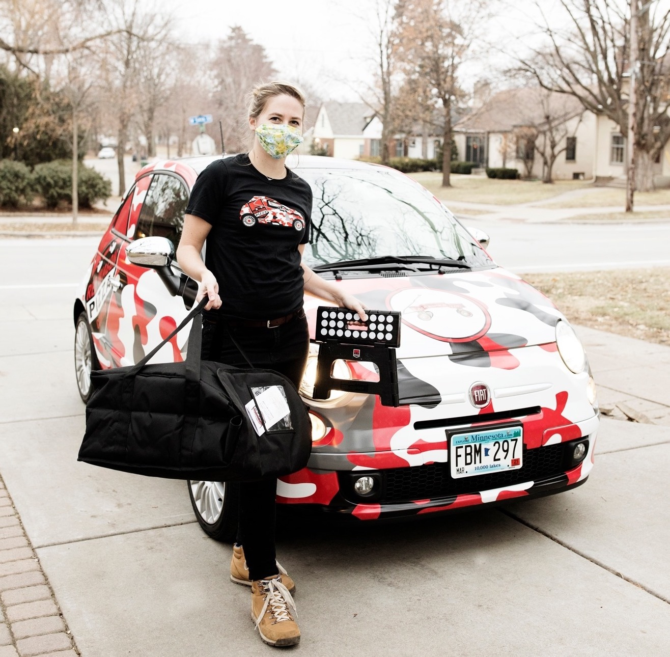 A woman carrying a pizza bag walks in front of a Fiat decorated with red, gray, and white camo pattern.