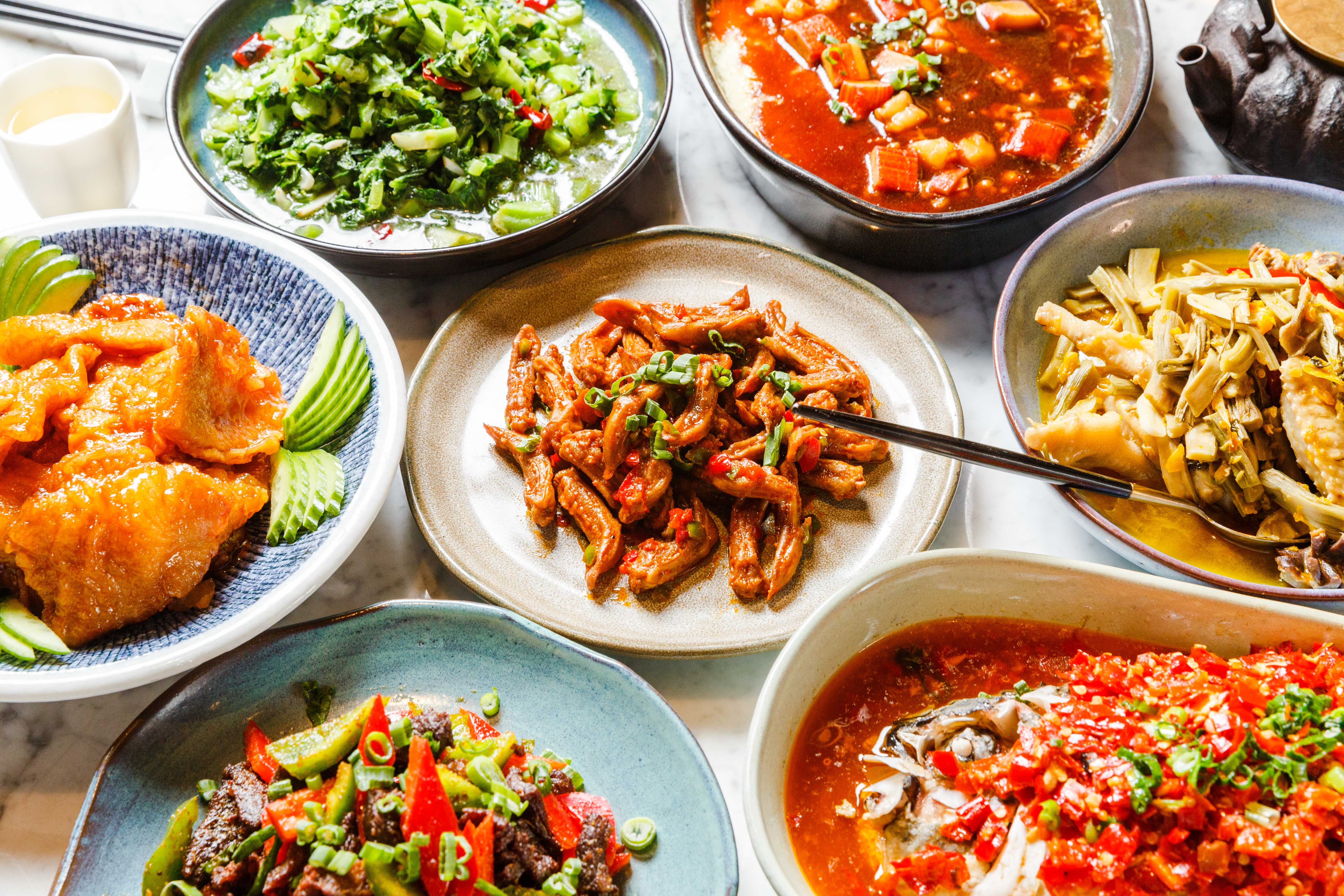 Eight assorted colorful dishes on plates.