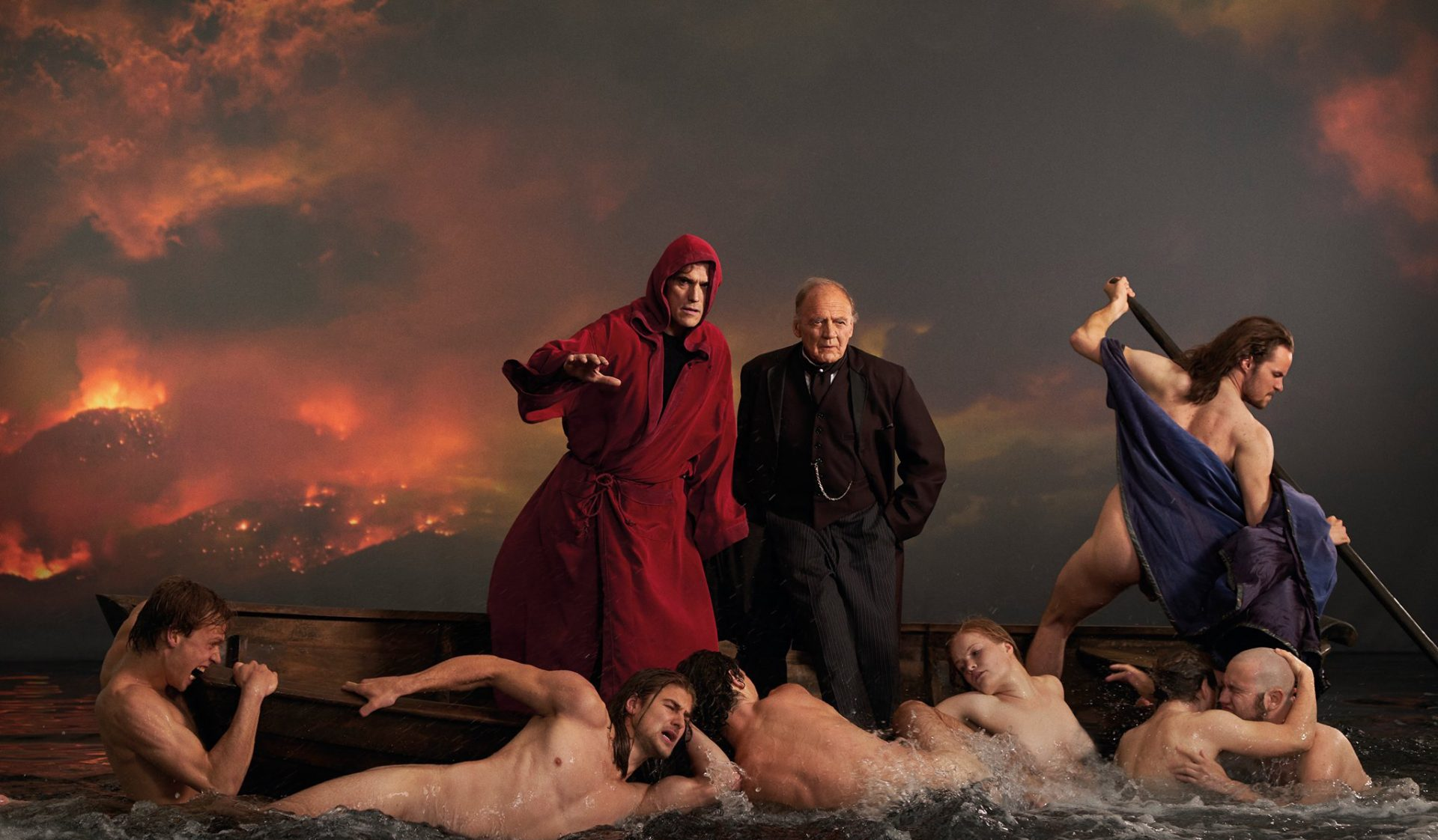 Matt Dillon, in a blood-red hooded robe, and Bruno Ganz, in a black suit, stand atop a boat as naked figures flail in the water below them, in a fantasy sequence mirroring classical Renaissance paintings.