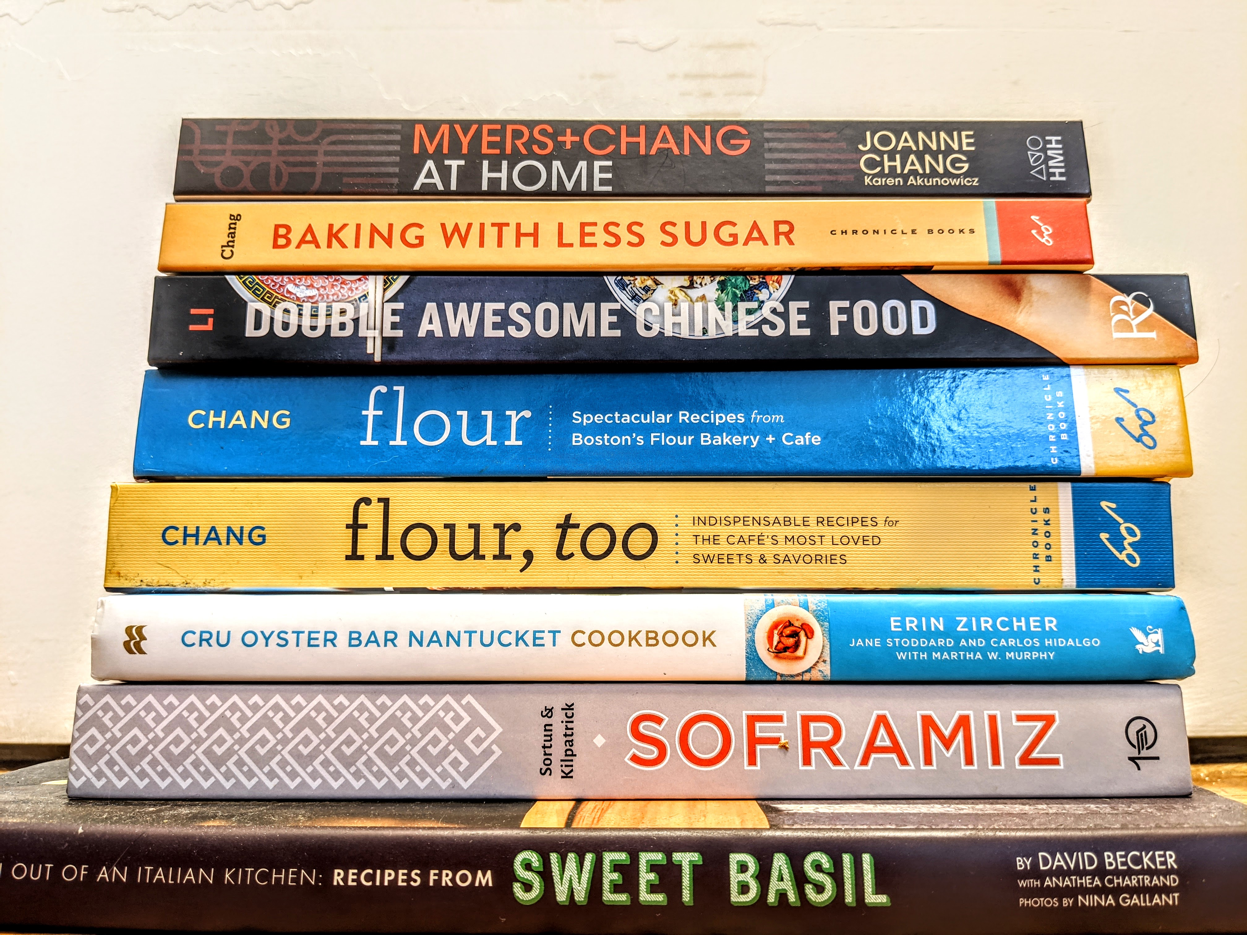 A stack of eight cookbooks, spines facing the camera, with titles including Sweet Basil, Soframiz, Double Awesome Chinese Food, and more