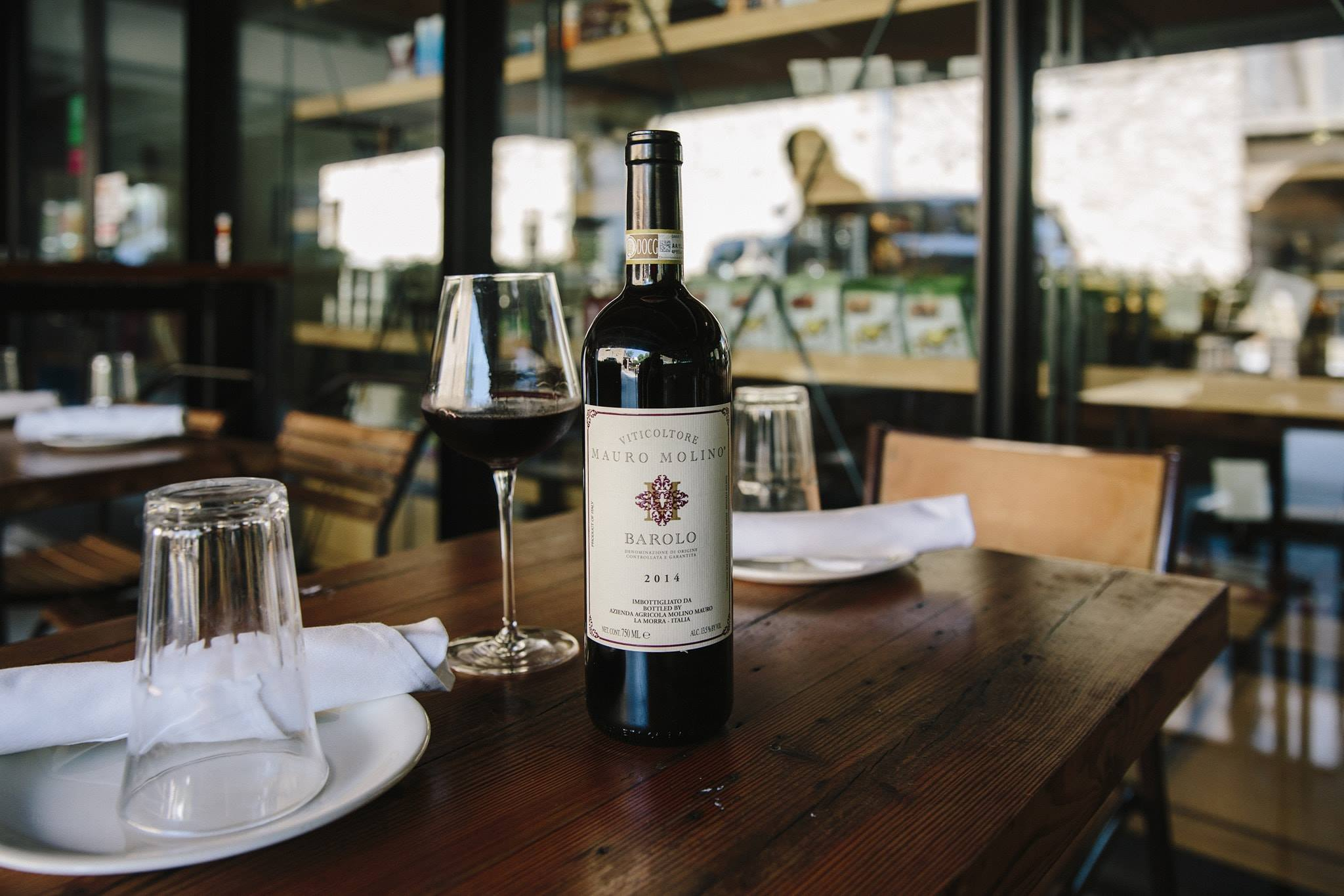 That outdoor patio at Storico Fresco in Buckhead with a bottle of red wine and wine glass on a table