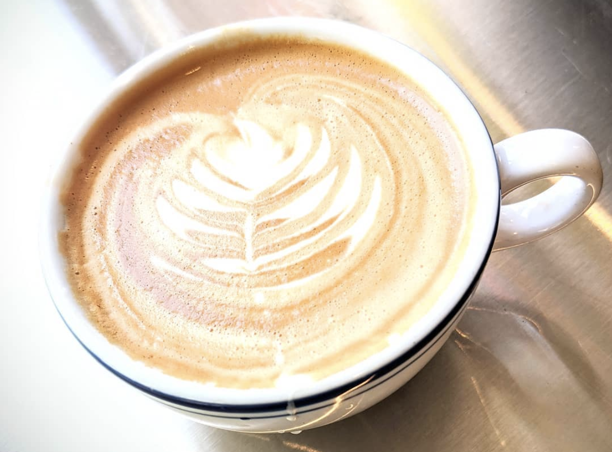 A coffee mug filled with a latte at Cortona Cafe
