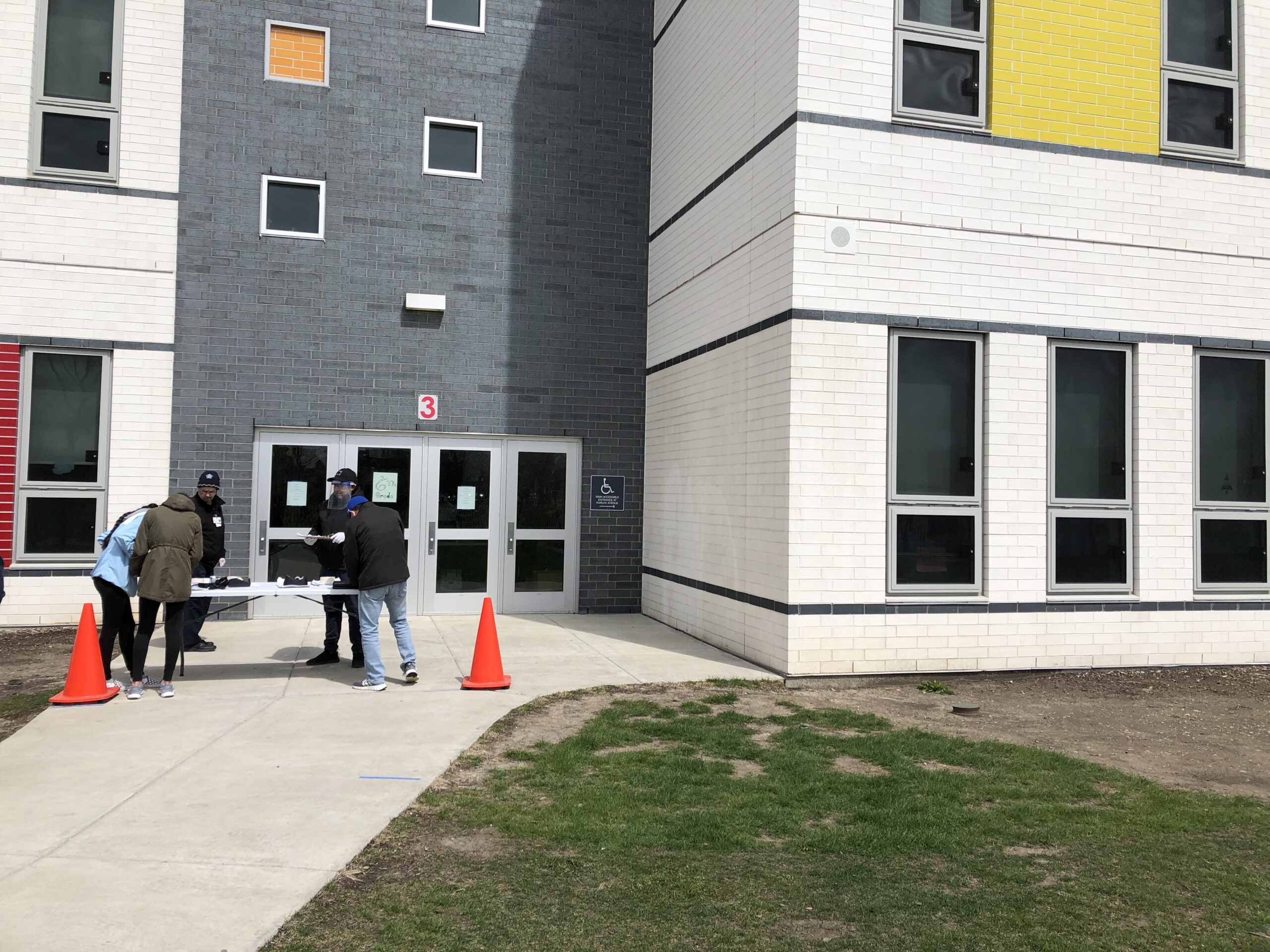 The Padilla sisters pick up loaner Chromebooks outside Richardson Middle School in Chicago on a blustery spring day.