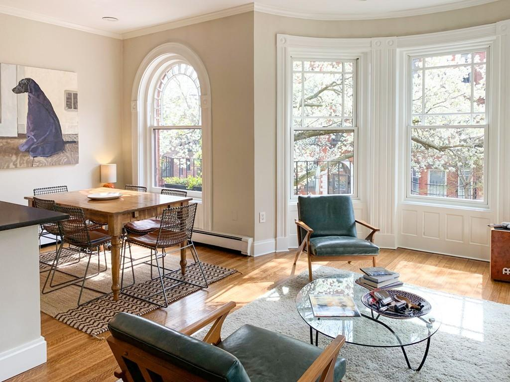 An open kitchen-dining-room-living-room area with furniture and a bay window.