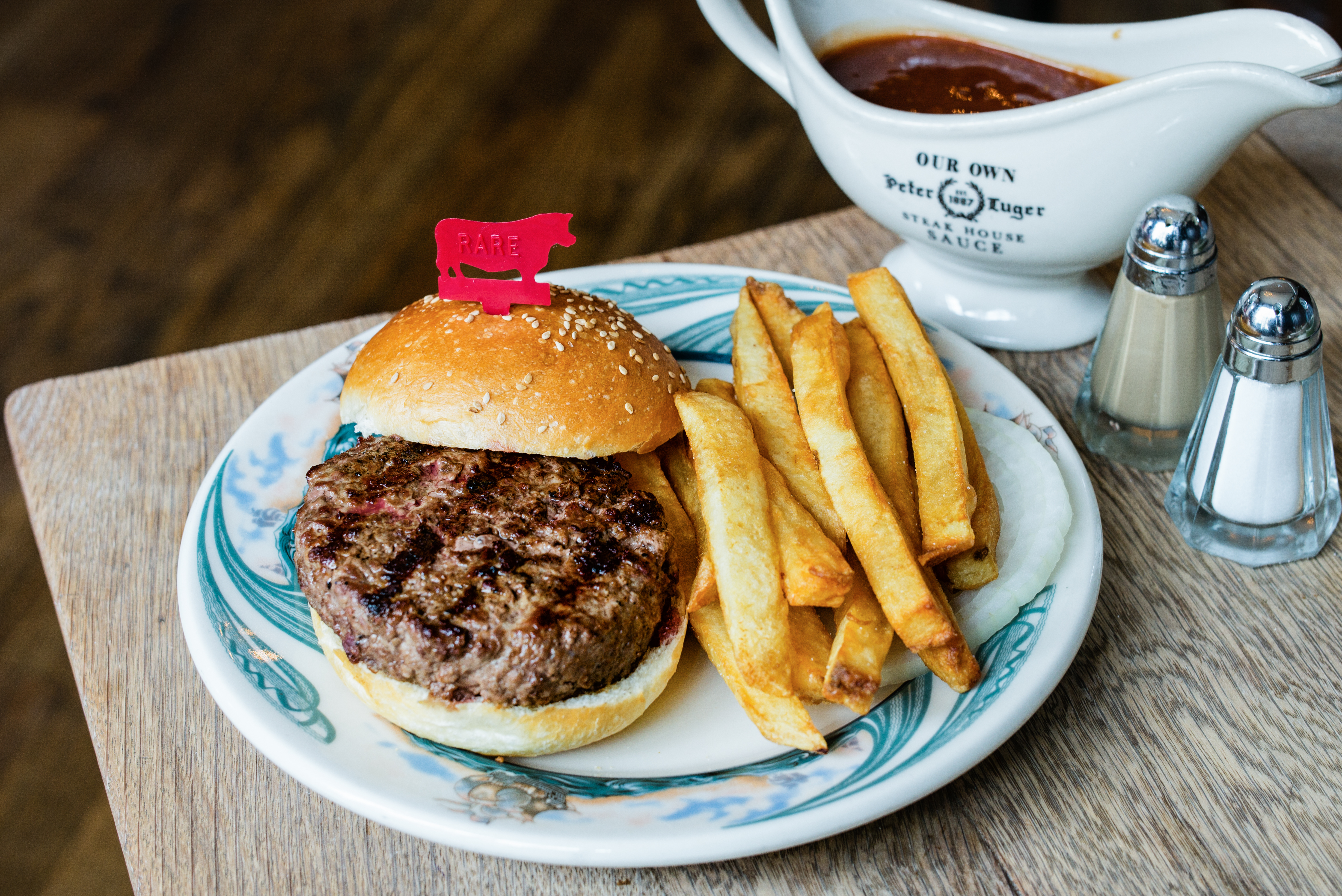 Peter Luger's hamburger with fries, on a white plate with blue markings