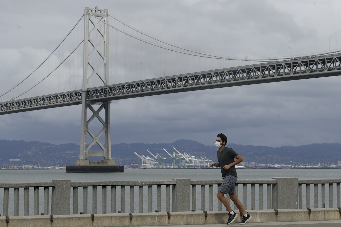 a man jogging on a sidewalk in front of a bay and bridge.
