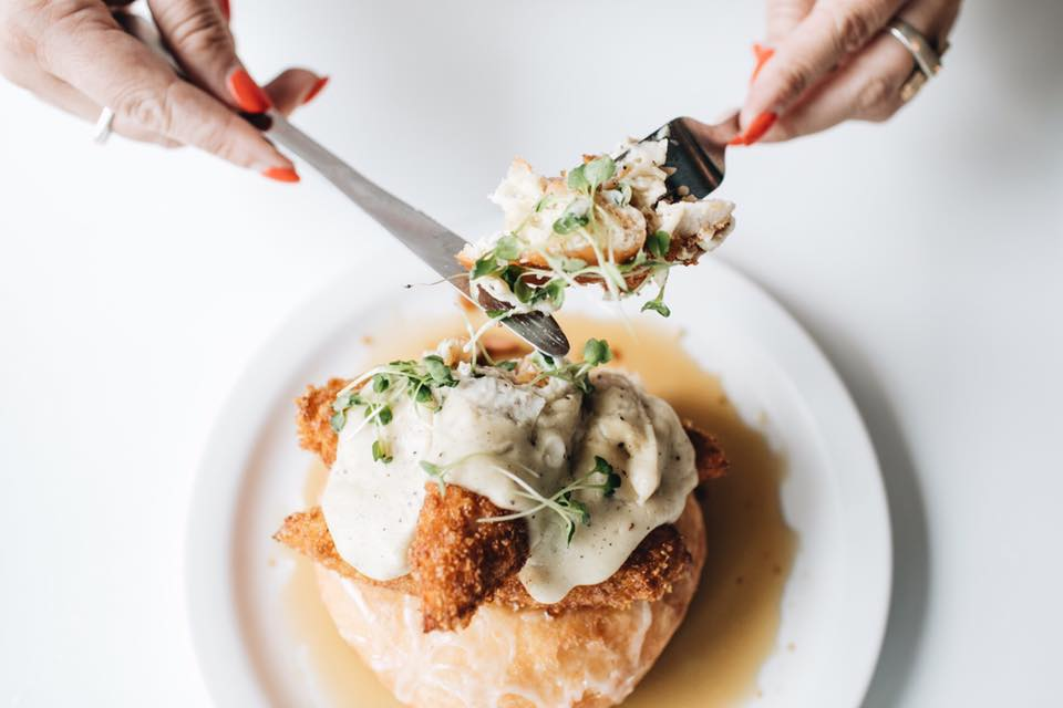 A doughnut topped with fried chicken and gravy