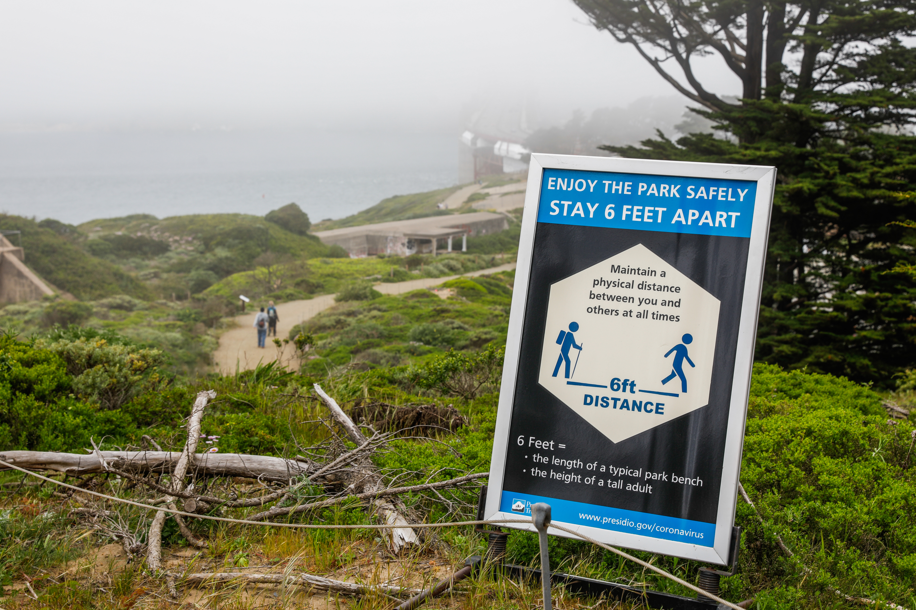 A blue and white sign on a nature trail warning hikers to keep six feet apart.