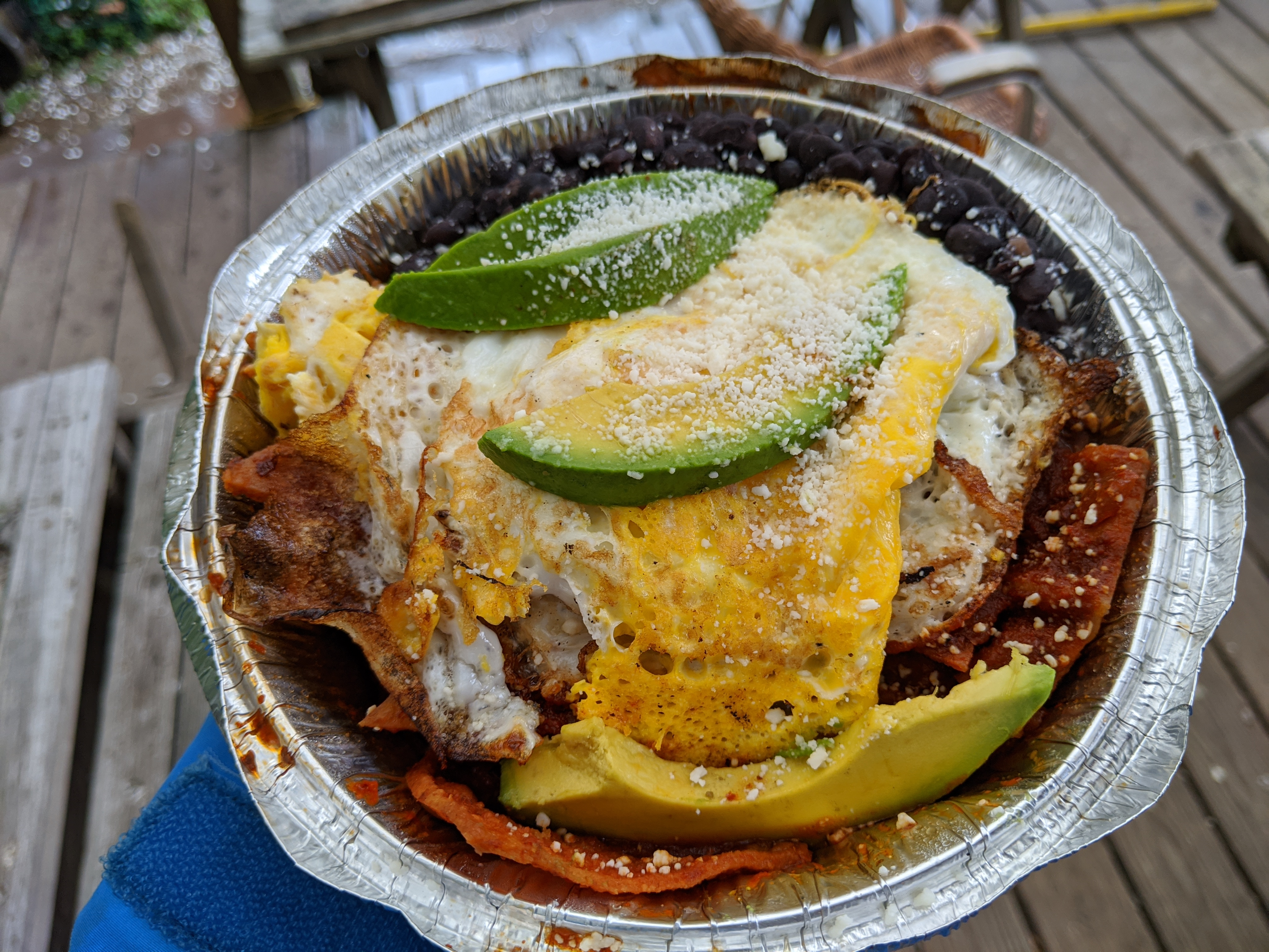 An aluminum tin of chilaquiles with avocado and eggs on top.