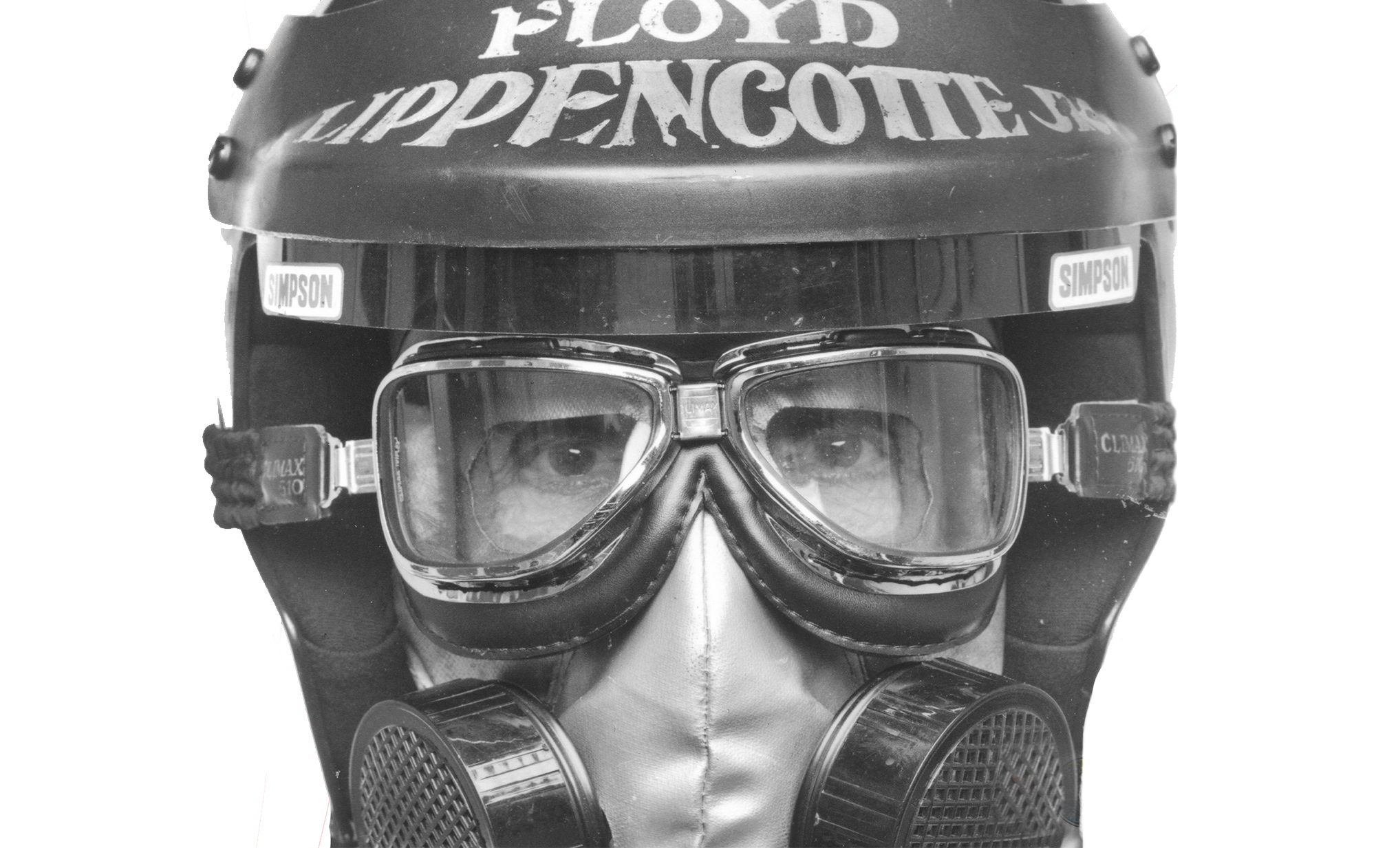 A close up black and white photo of Bob Muravez's face as Floyd Lippencott, wearing a racing helmet and facemask, staring straight into the camera.