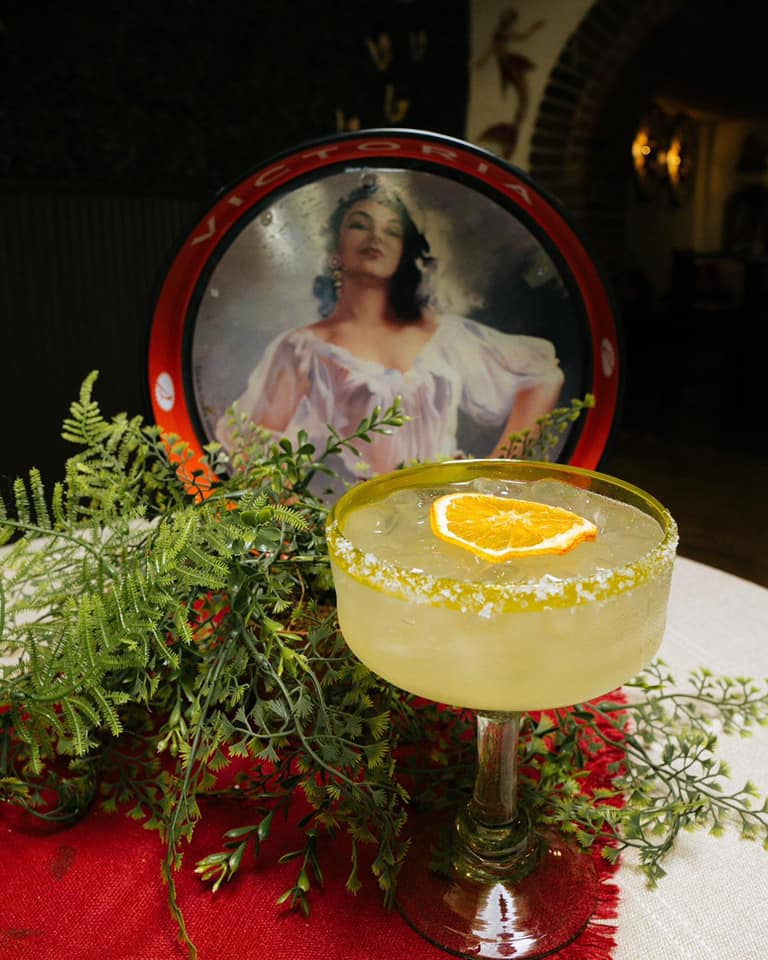 A margarita with an orange wheel garnish in front of a picture of a senorita