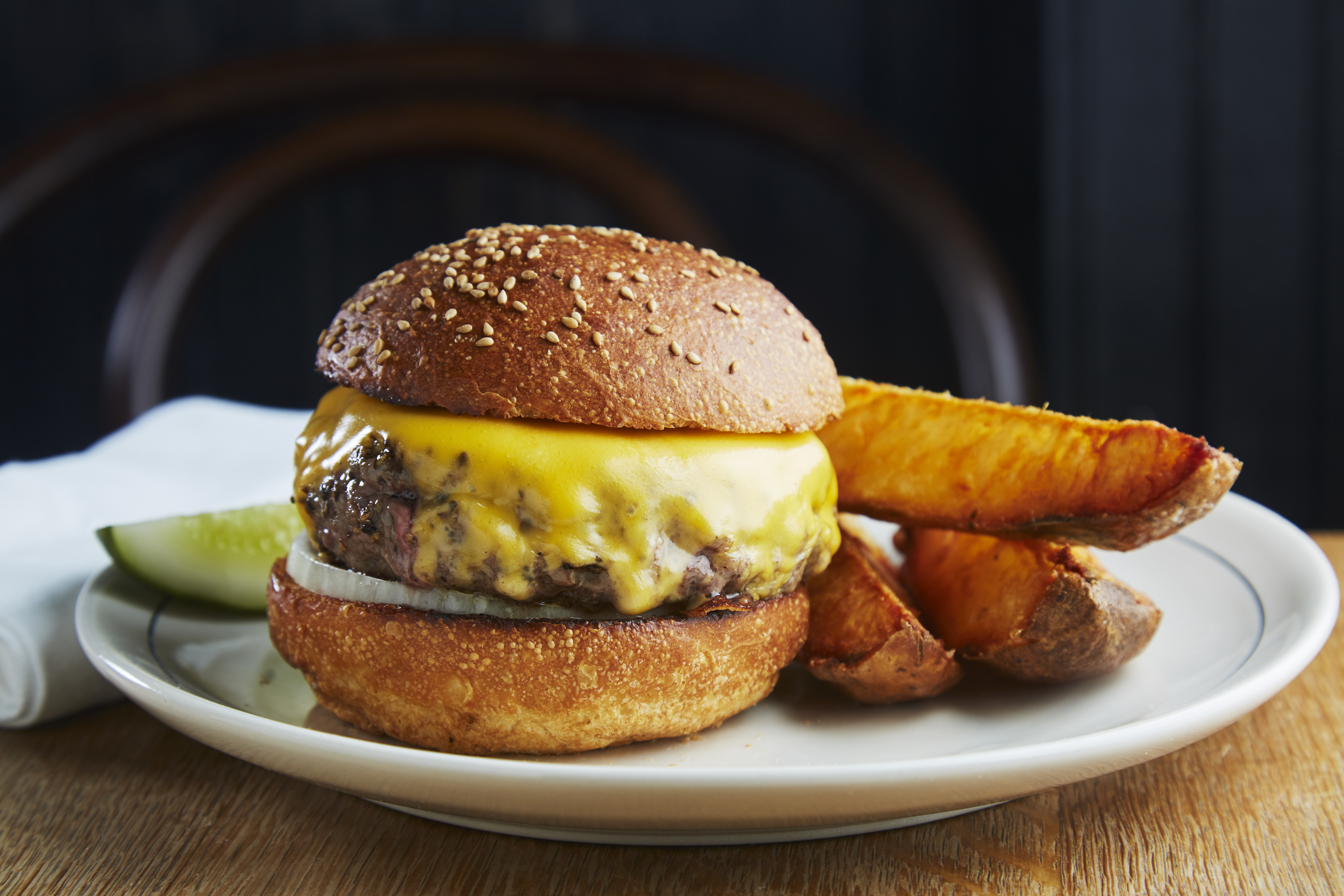 The Red Hook Tavern burger, American cheese melting down the side, sits on a white plate next to three wedge fries