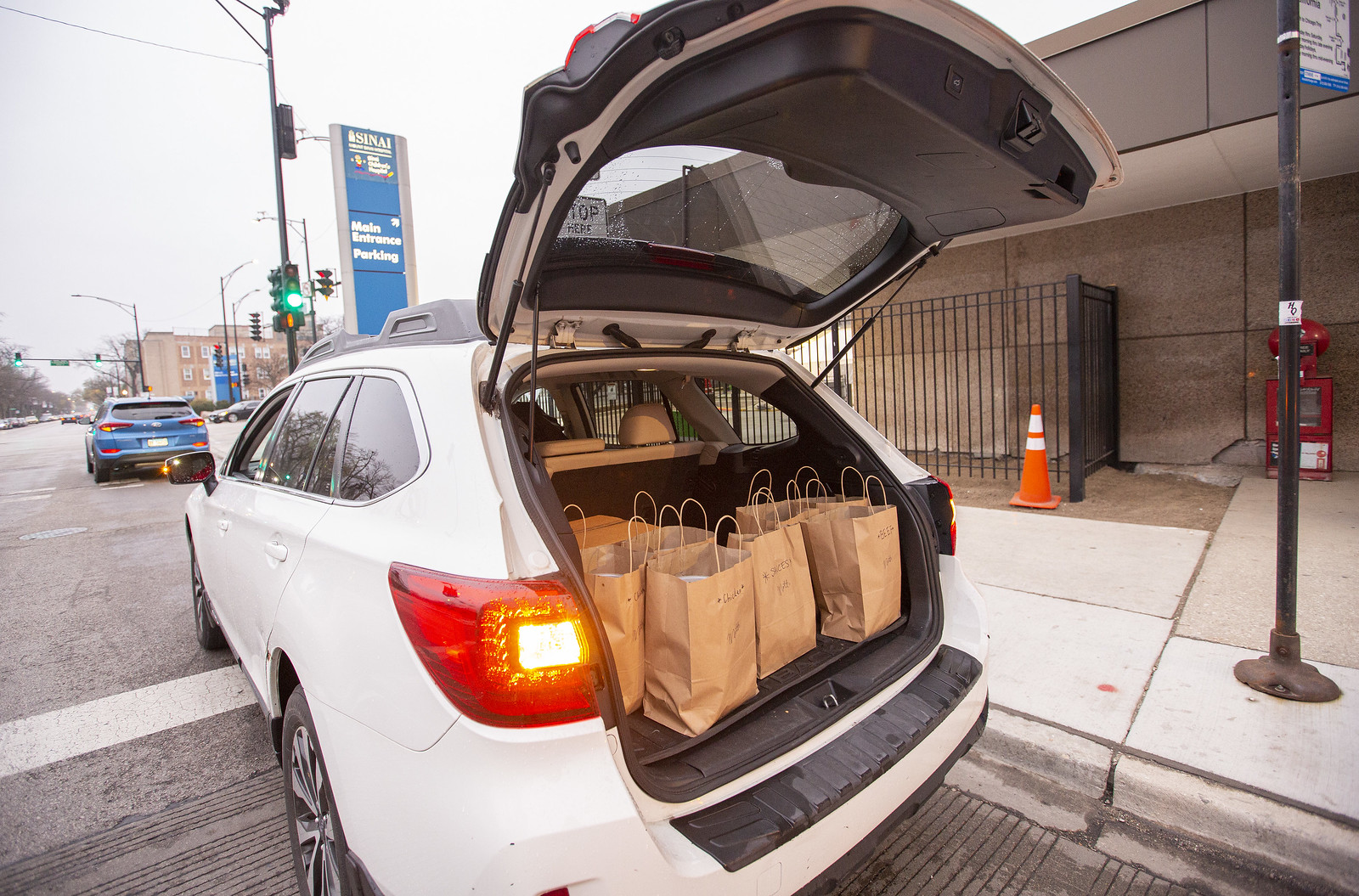 An SUV trunk open with a vehicle full of brown bags.