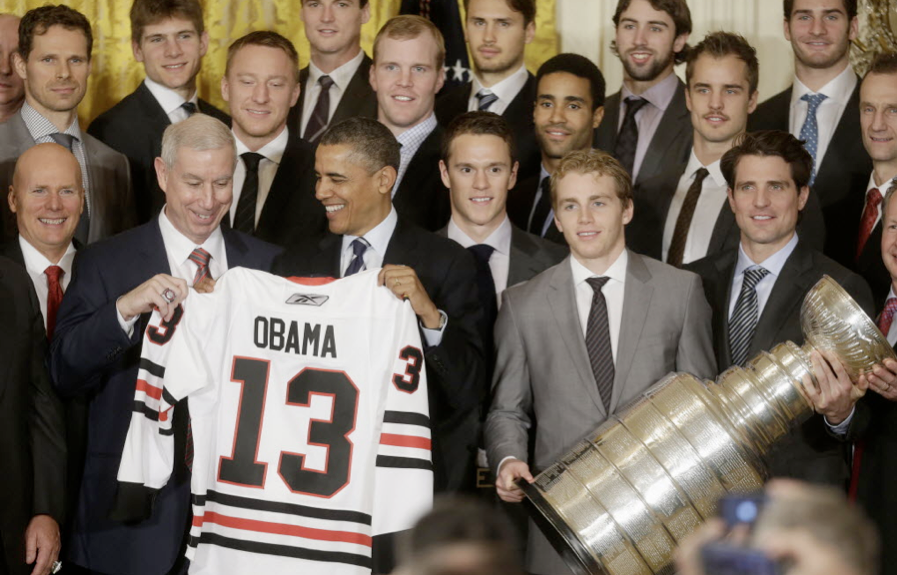 Blackhawks President and CEO John McDonough, left, presents a jersey to President Barack Obama during a ceremony in the East Room of the White House on Nov. 4, 2013.