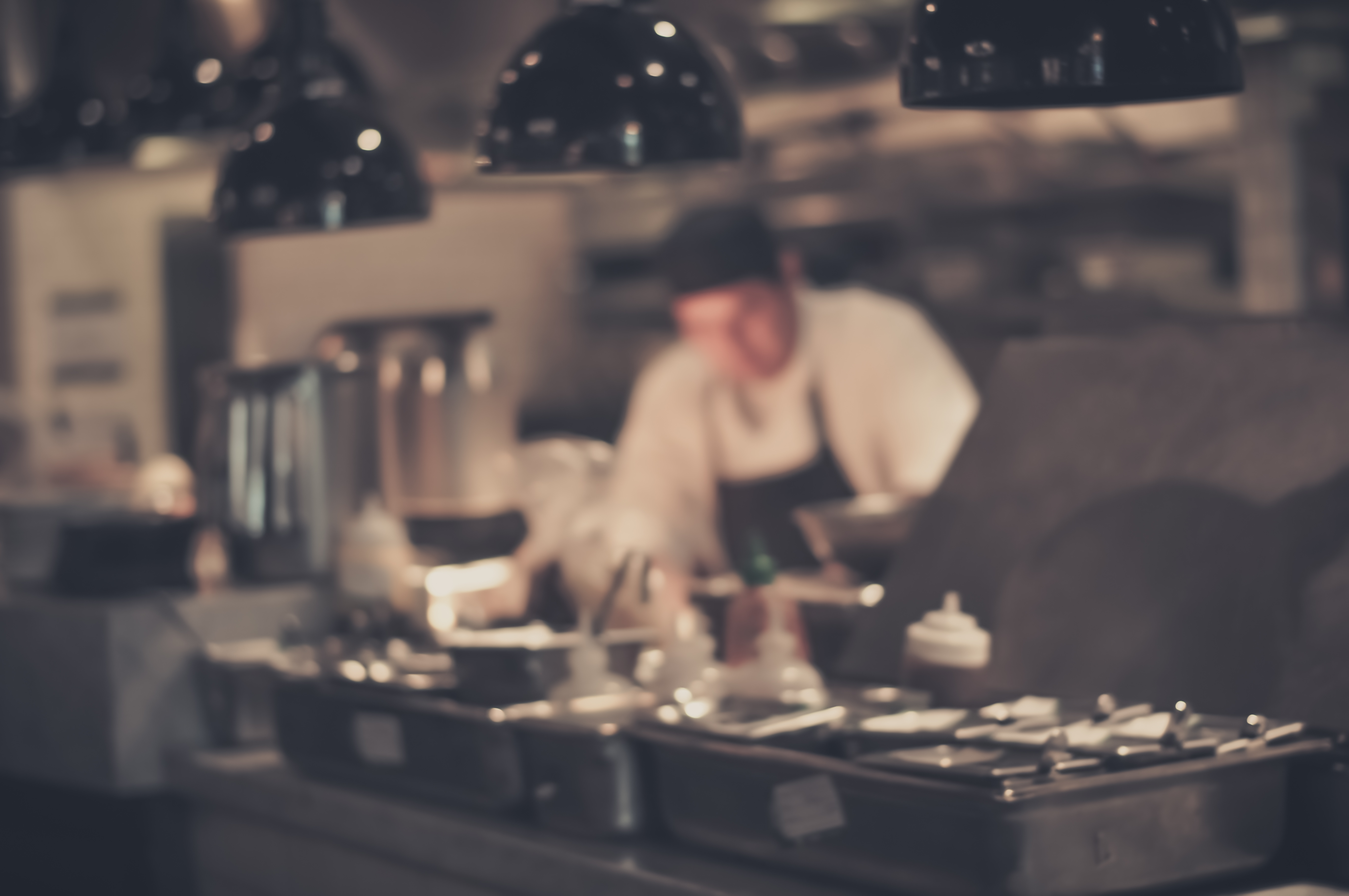 blurred image of cook in restaurant with prep items in the foreground