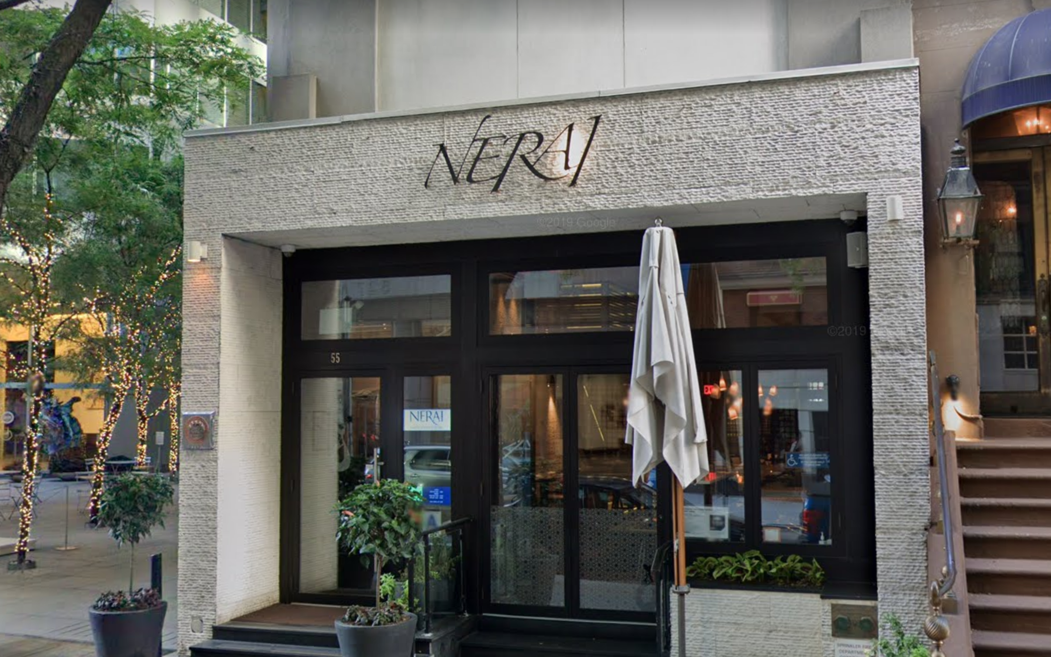 The stone-clad exterior of a greek restaurant called Nerai. An outdoor seating umbrella is placed in the front.