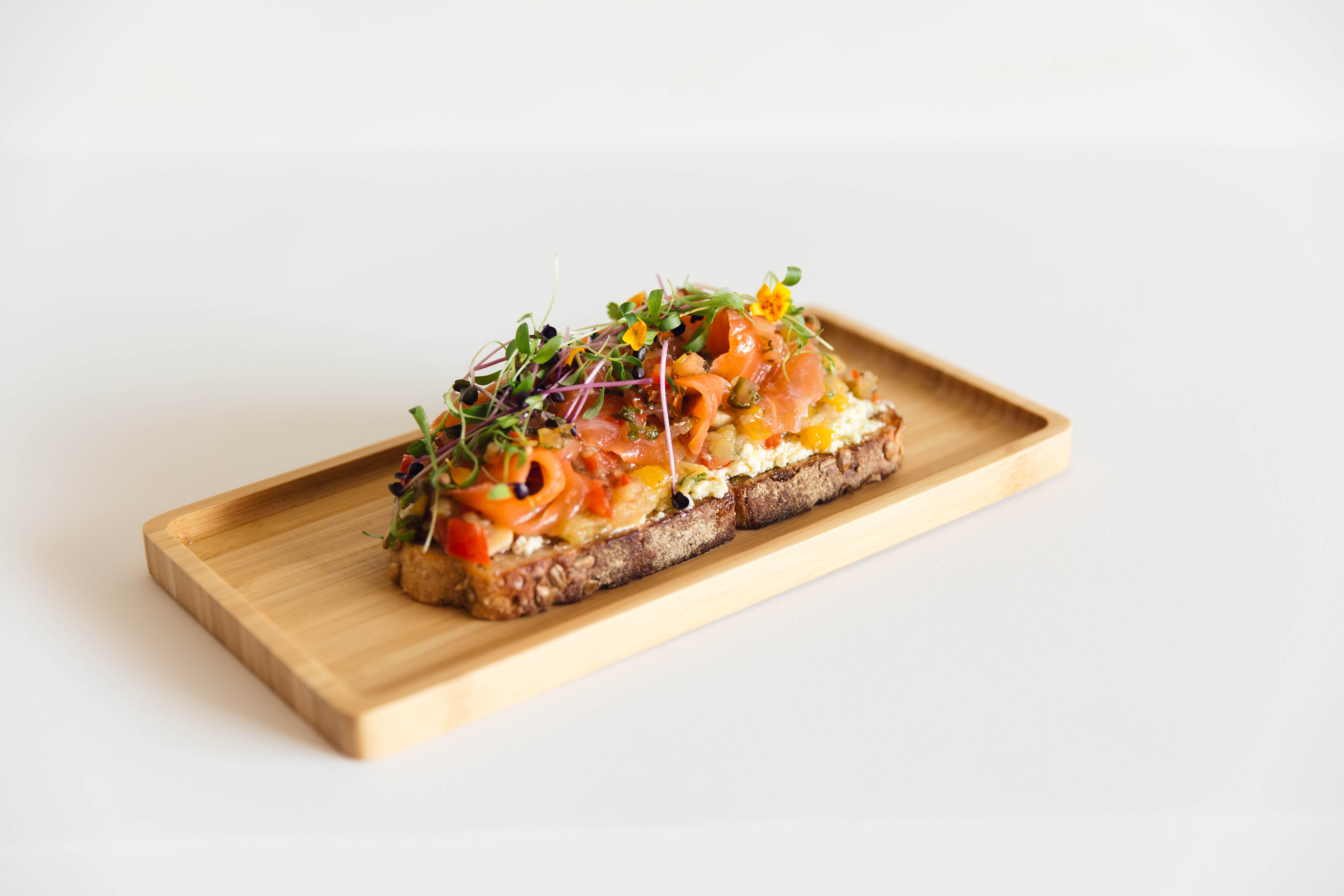 The Patagonian Goat toast from Zumo includes salmon cured in Peruvian pisco, baked goat cheese spread, pisto, and chimichurri