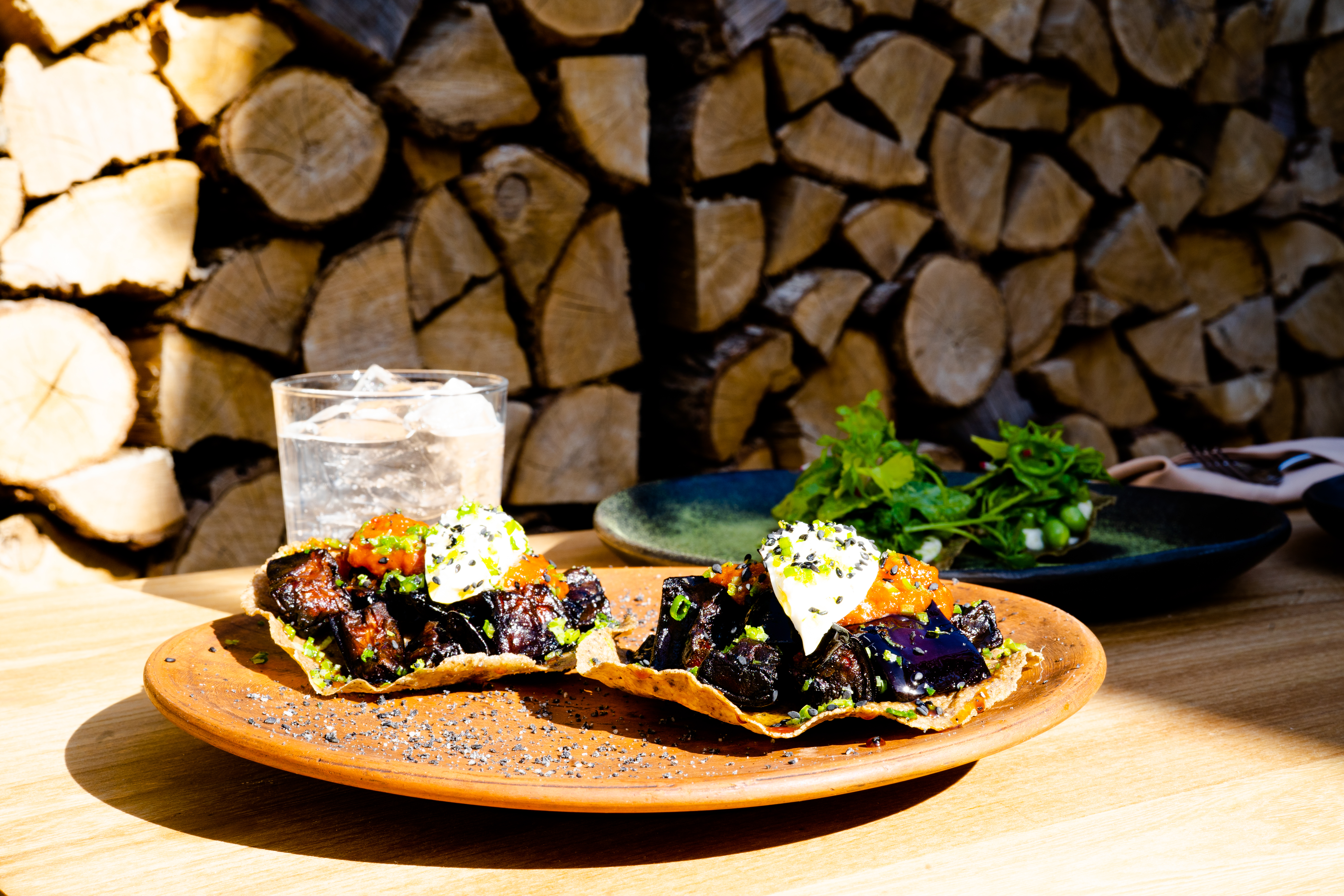 Two crispy corn tortilla tacos on a sunny patio with a full wine glass