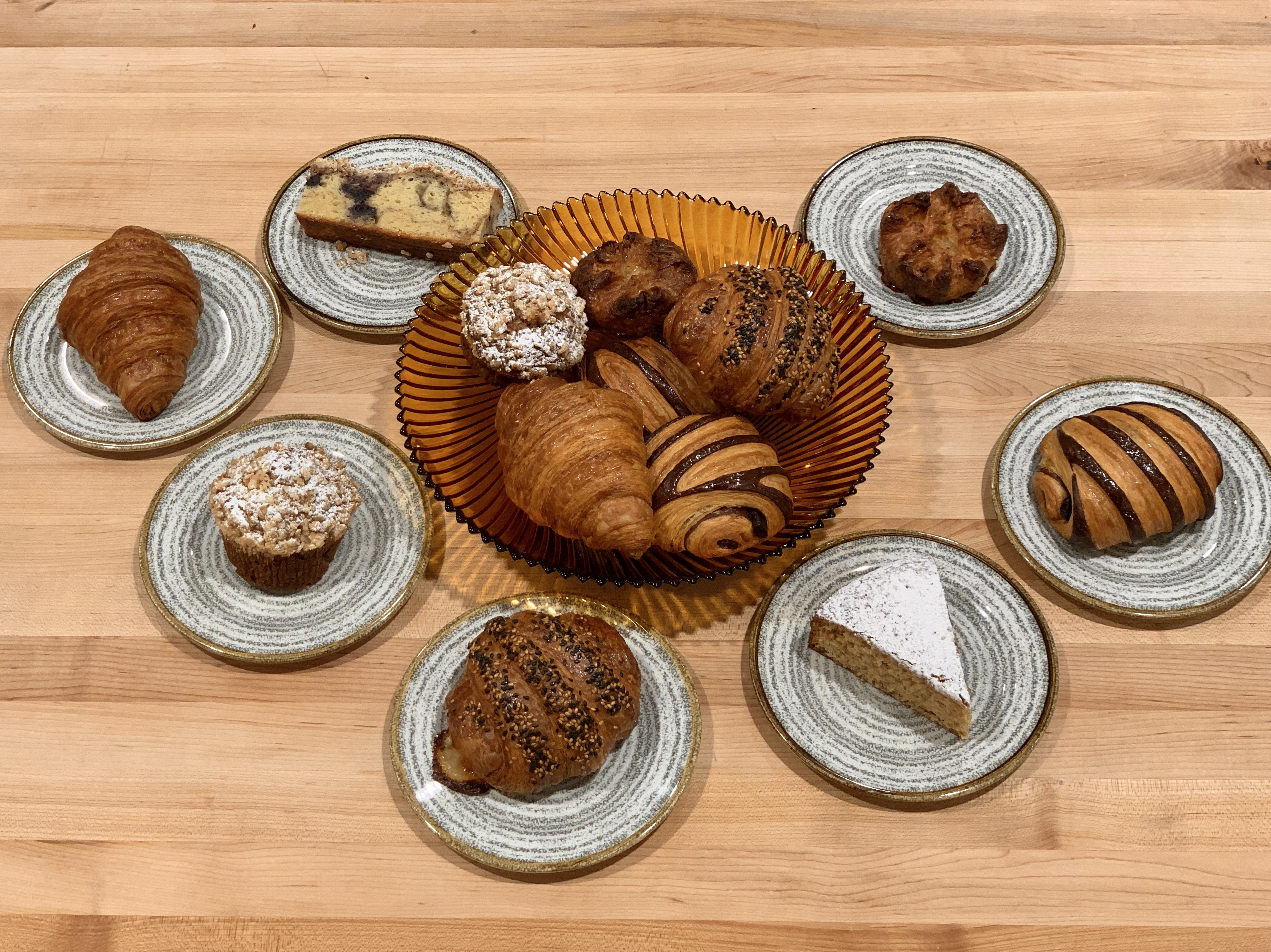 A wooden table filled with plates of baked goods