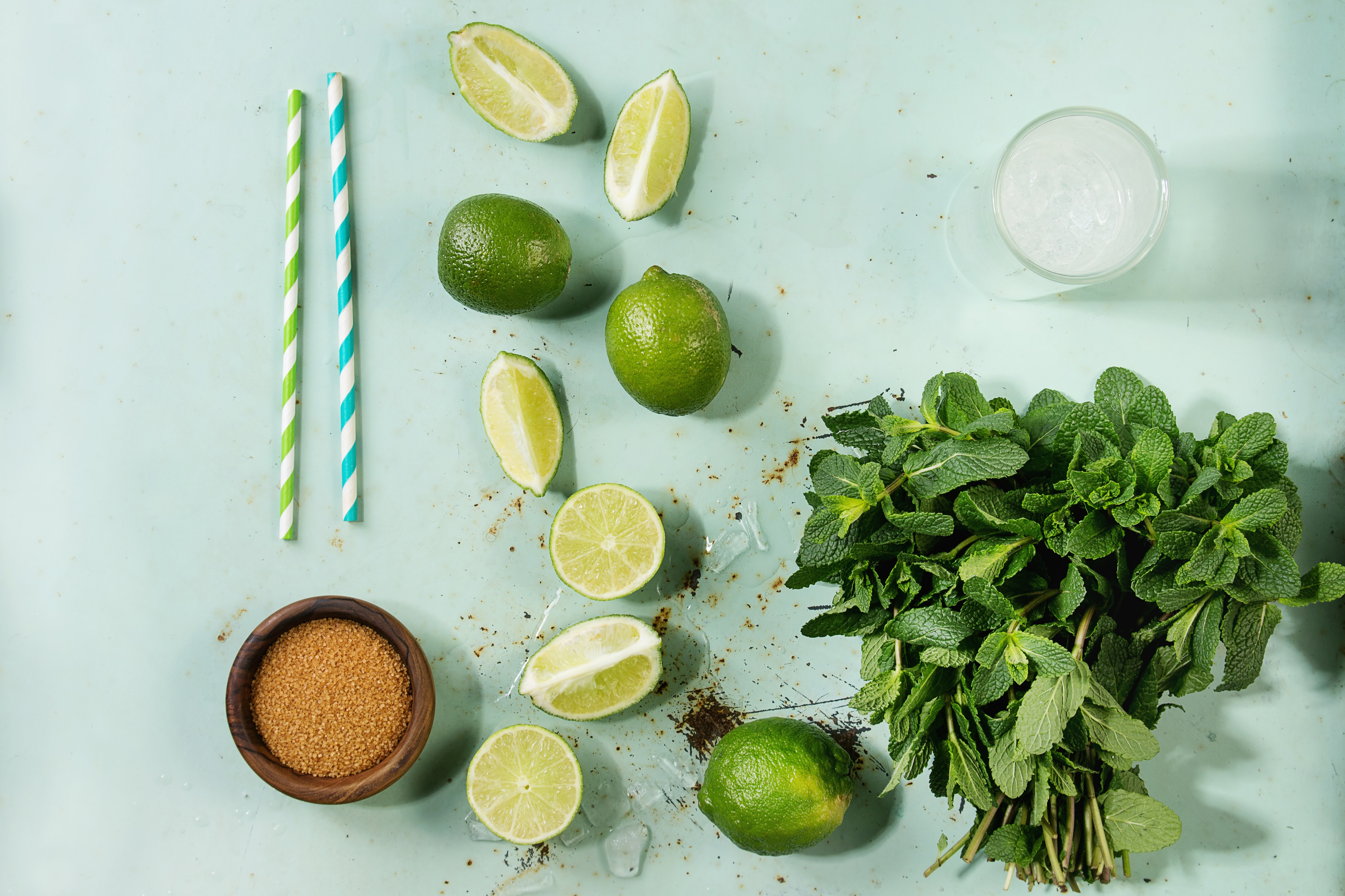 Ingredients for making mojito cocktail Bundle of fresh mint, limes, brown sugar, crashed ice cubes, glass of soda water, cocktail tubes over green pin up background Top view, space Food knolling