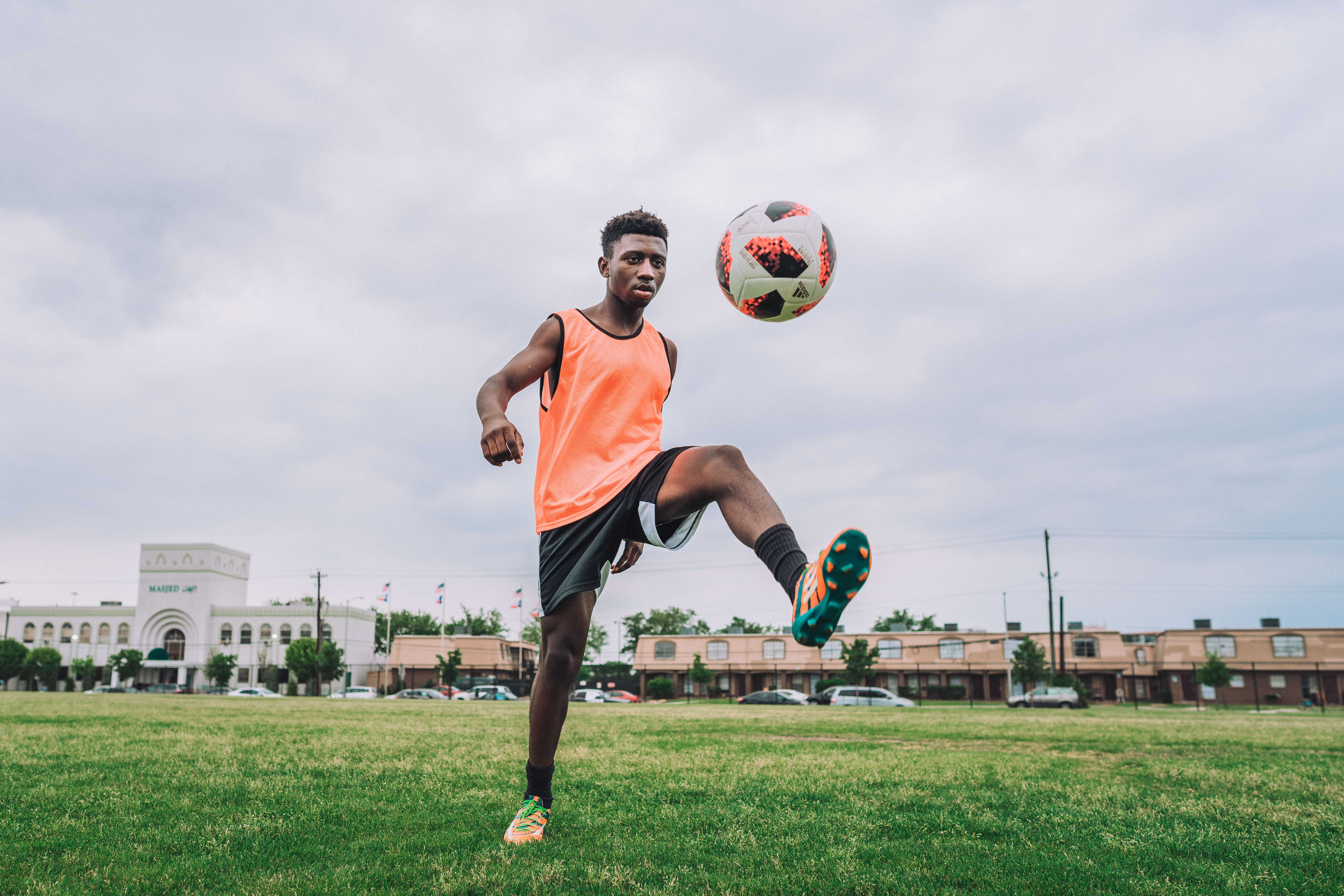 A refugee soccer player in an orange tank top juggling a soccer ball on an empty field in Houston.