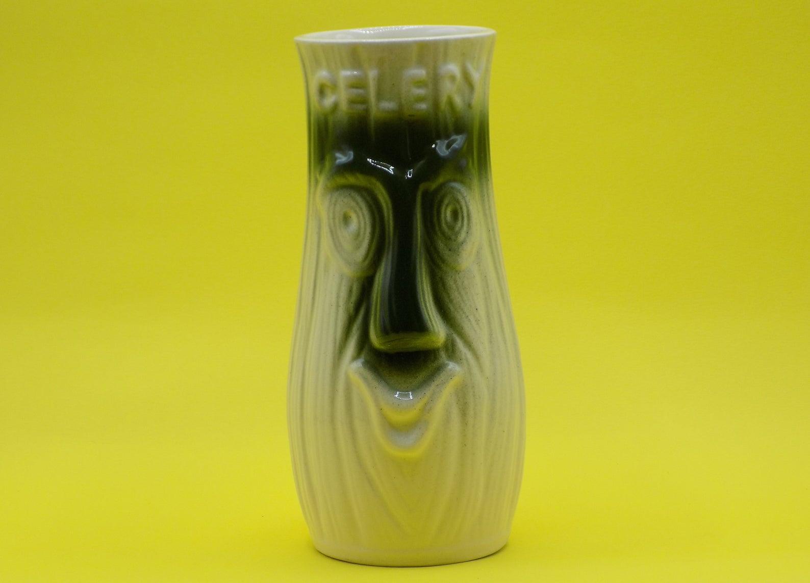 A vintage celery vase, shaped like celery with a face