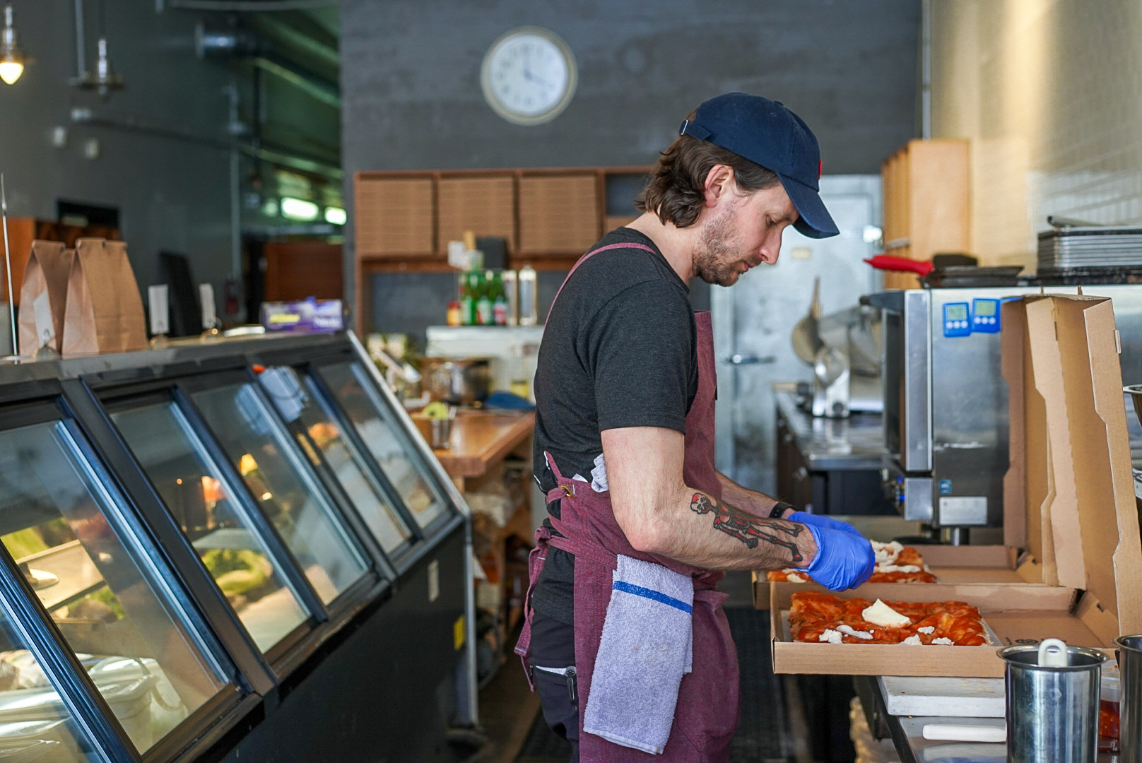 A worker prepares pizzas in to-go boxes inside a cafe