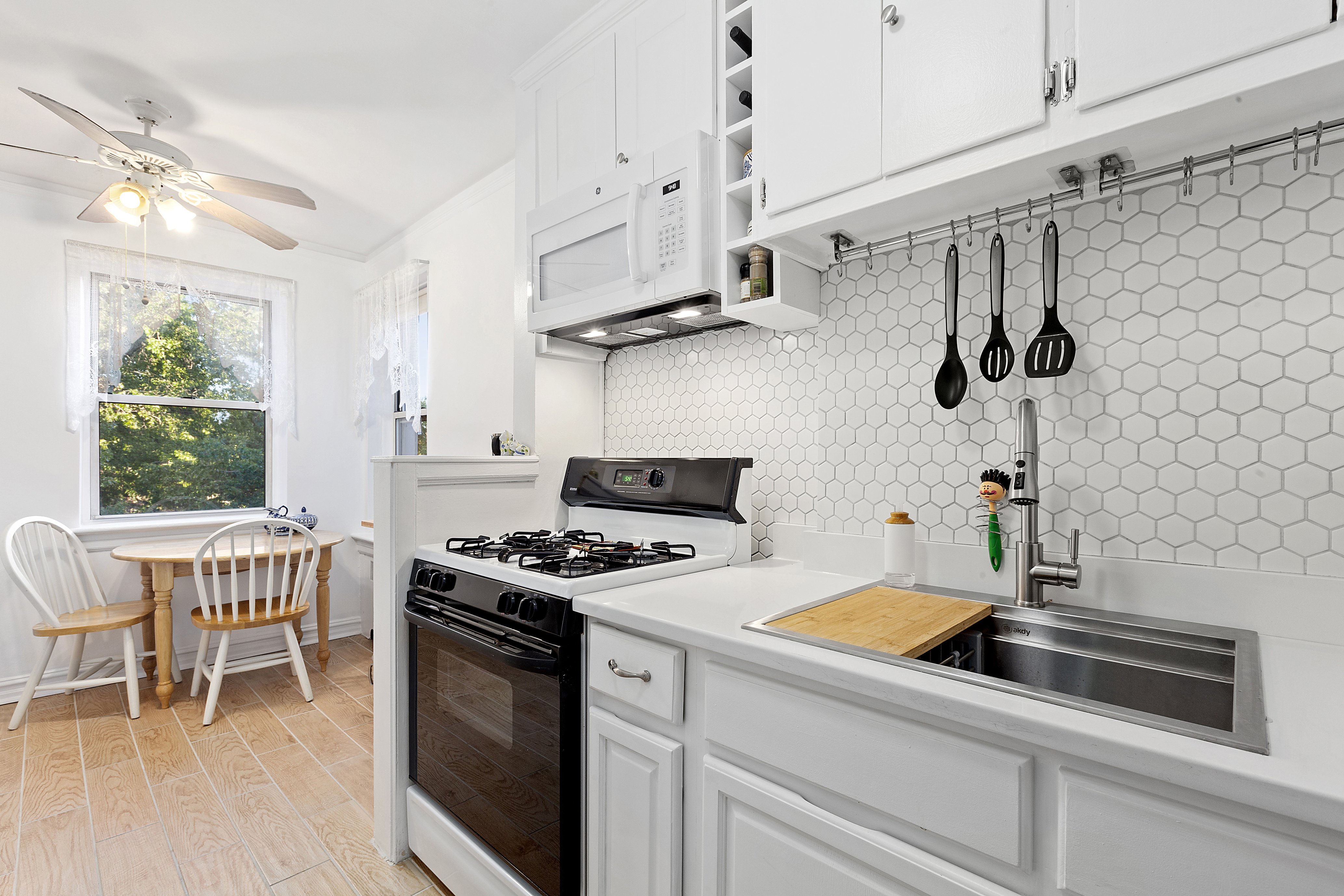 A kitchen with hardwood floors, a small dining table, a window, a ceiling fan, and white cabinetry.