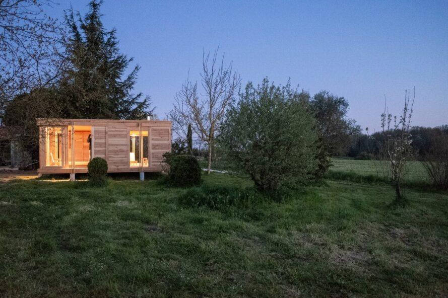 Timber tiny house glowing at dusk.