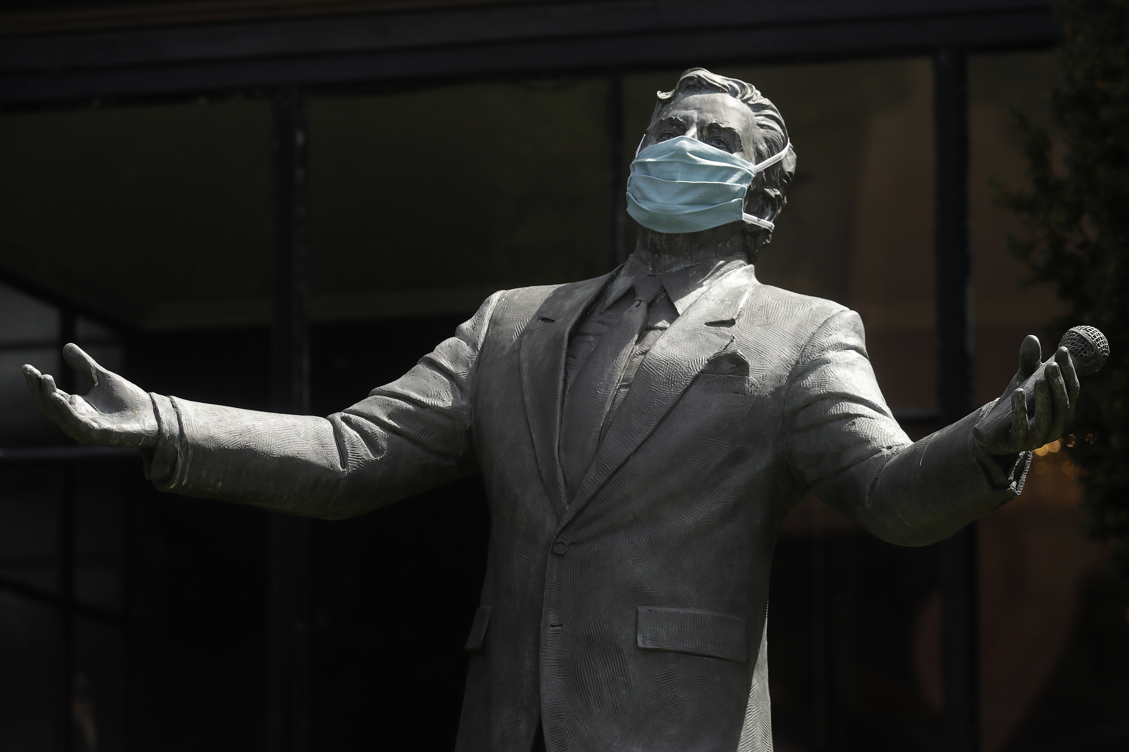 A face mask covering the face of a bronze statue of a man.