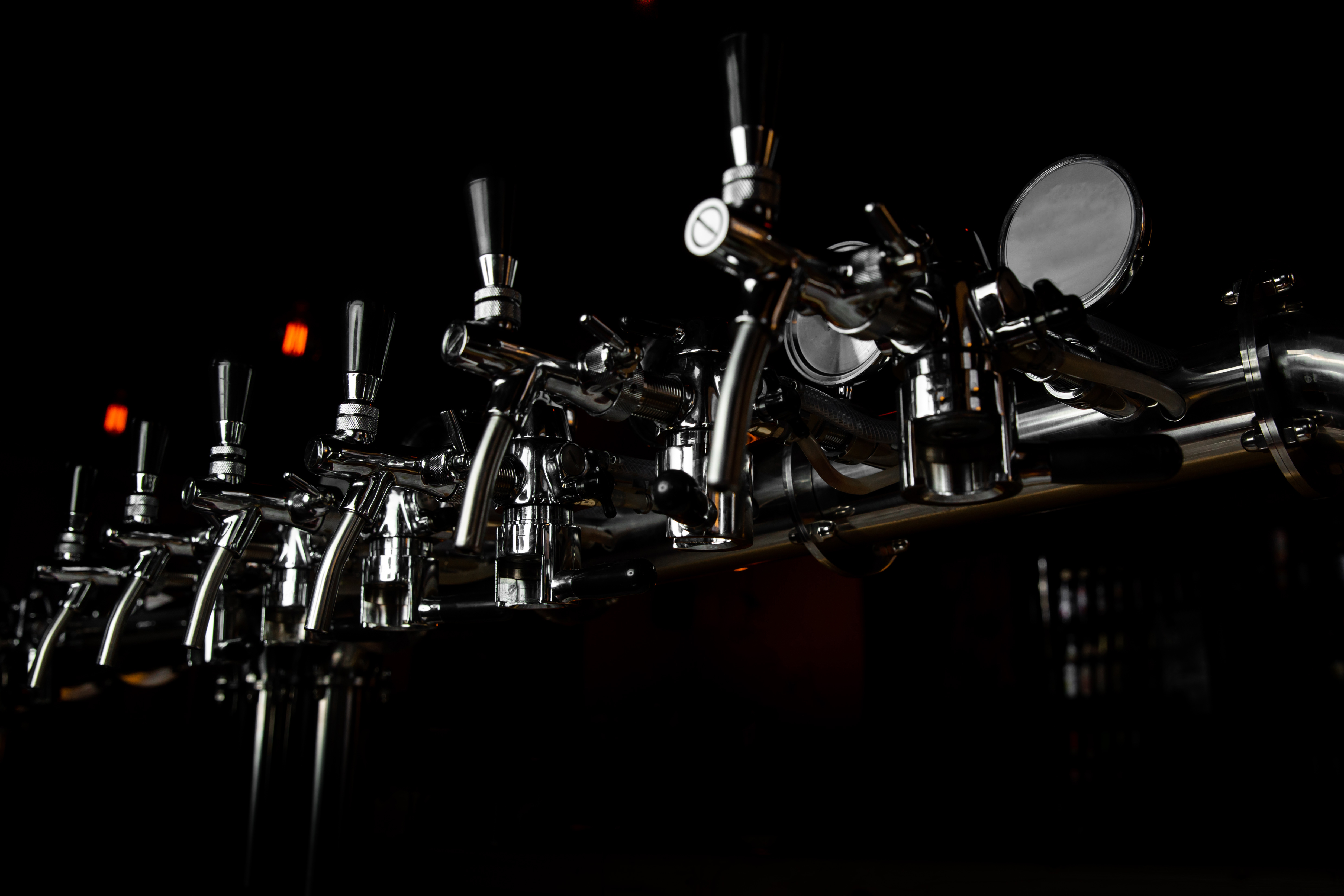 A view of taps in a darkened brewery