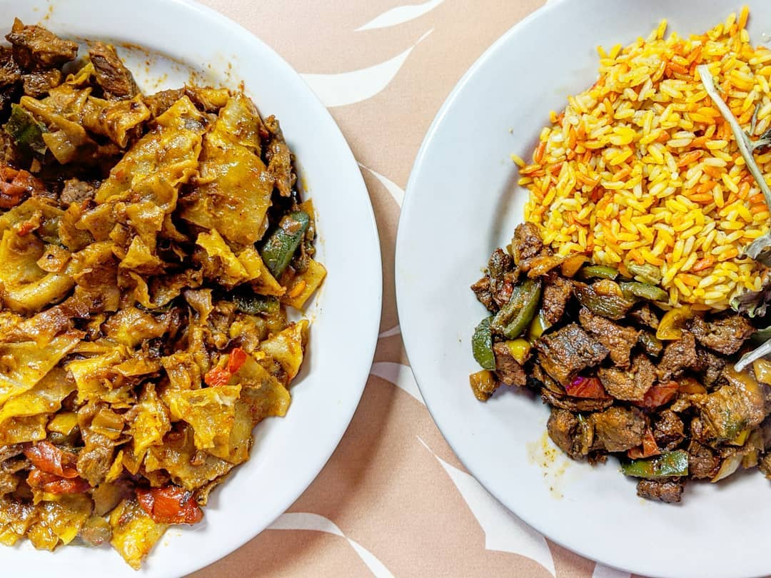 Overhead view of two Somali dishes on a pale peach tablecloth with white accents. One dish is chapati strips cooked in a tomato sauce with chunks of beef; the other is a beef biryani with multi-colored rice in shades of yellow and orange.