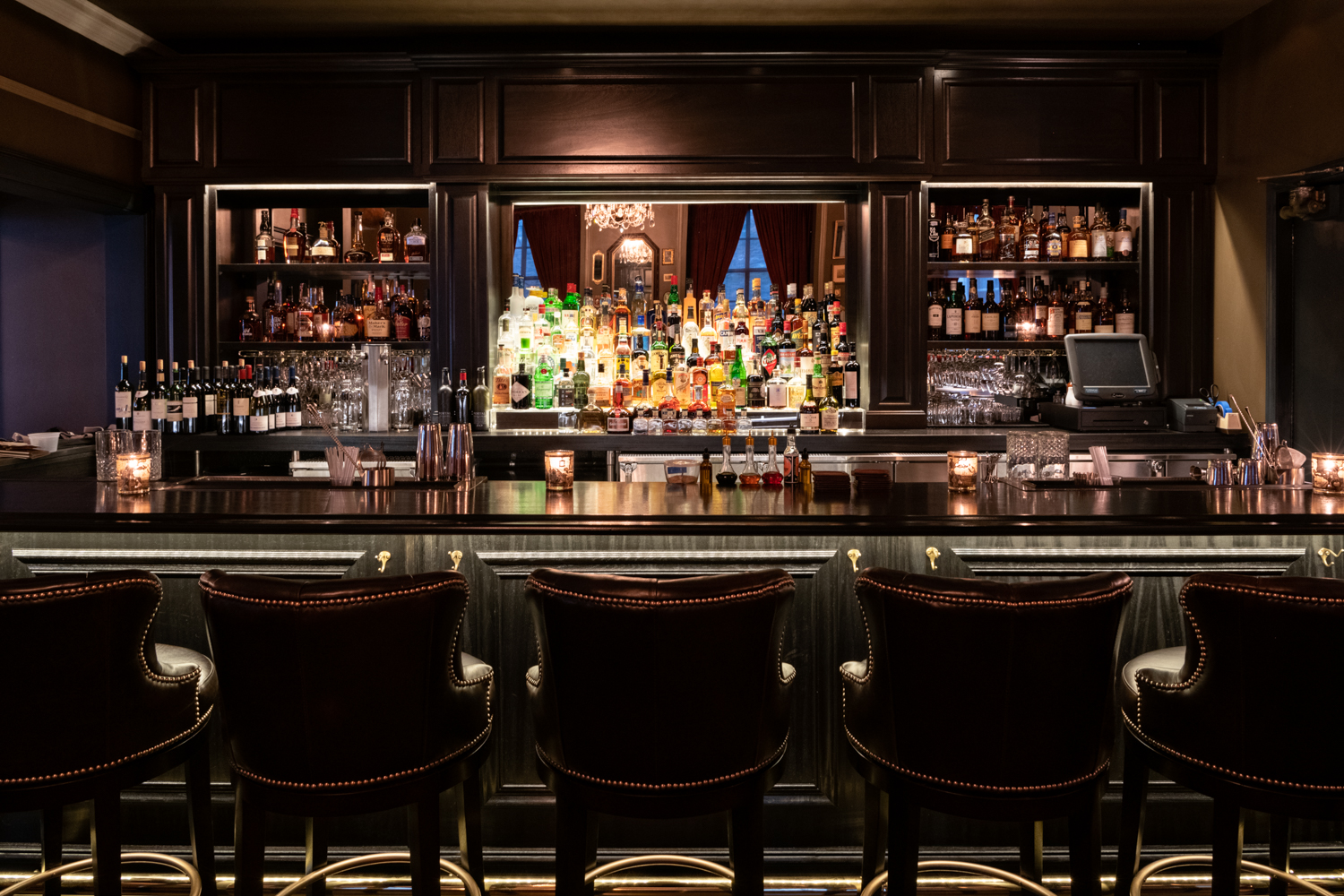 A dark bar lined with substantial chairs