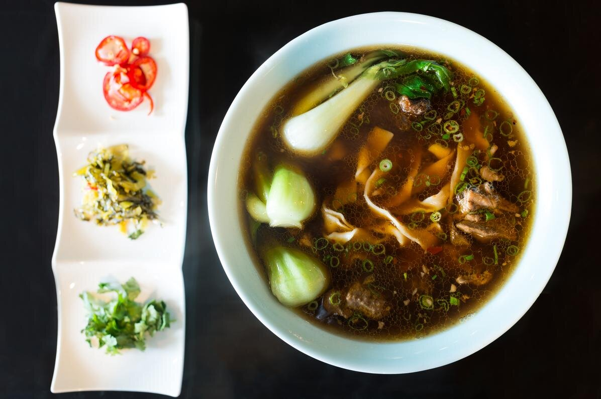 A top-down view of beef noodle soup at Facing East, with a selection of side toppings