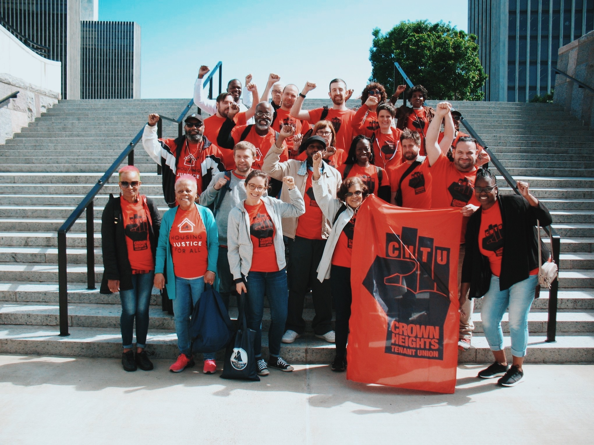 A group portrait of the Crown Heights Tenants Union standing on a concrete staircase. holding a banner There are about two dozen people all wearing red shirts and raising their fists.