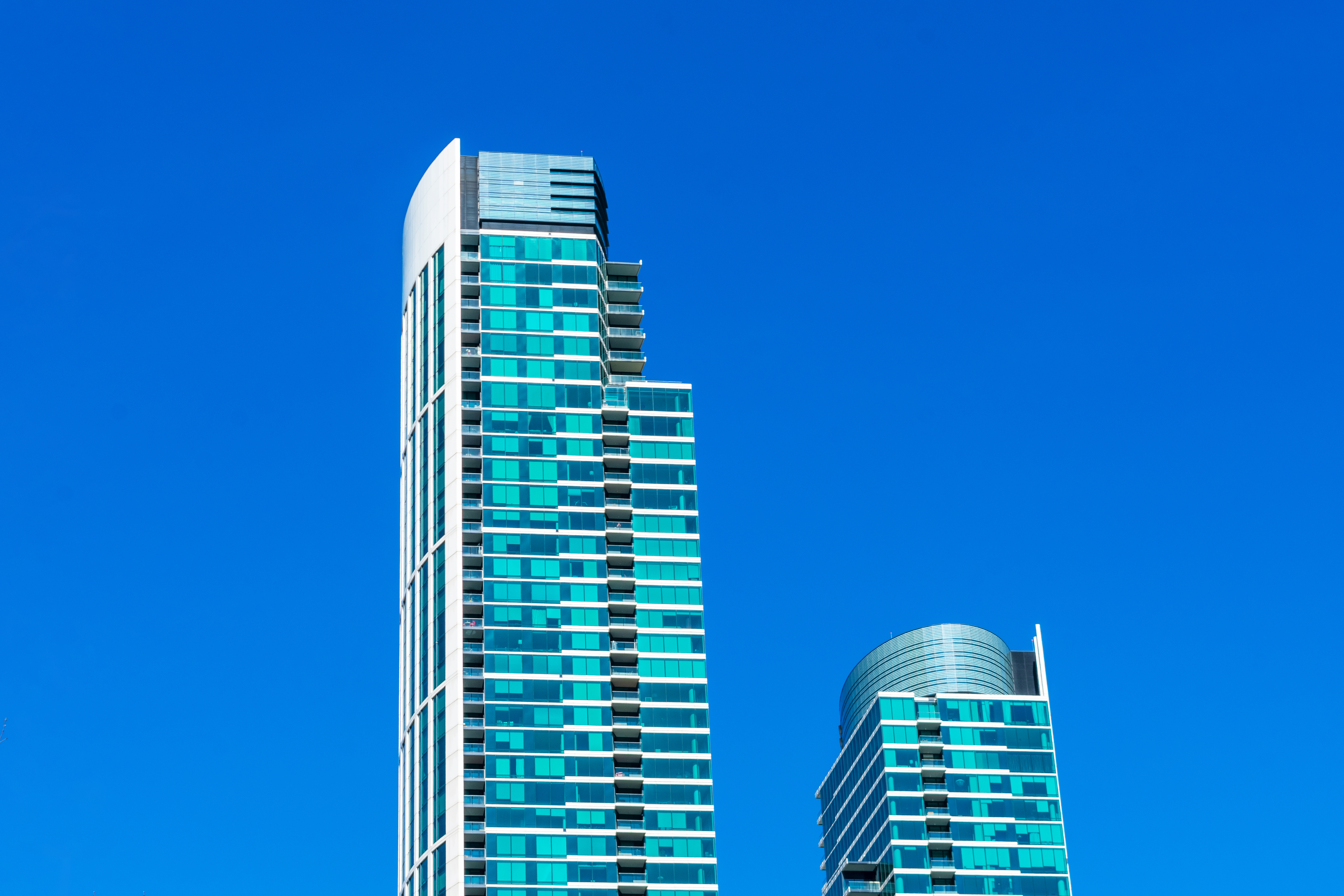Two glassy, blue towers against a blue sky.