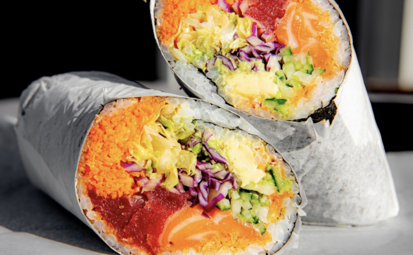 A sushi burrito filled with raw salmon and various vegetables