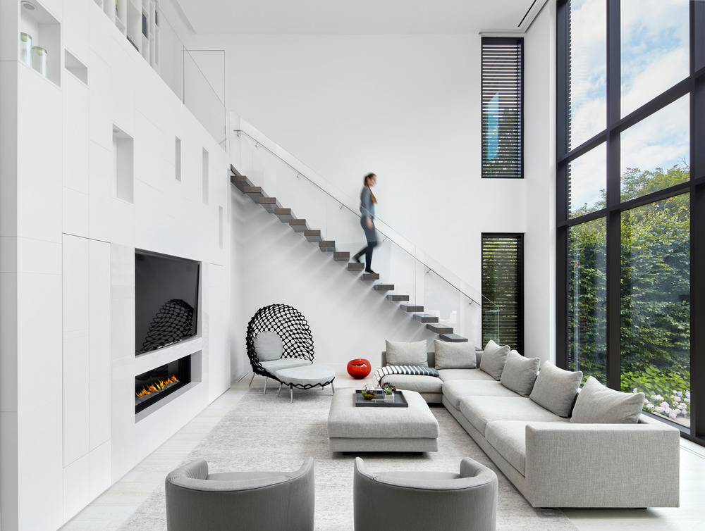 Woman walking down floating staircase into living room.
