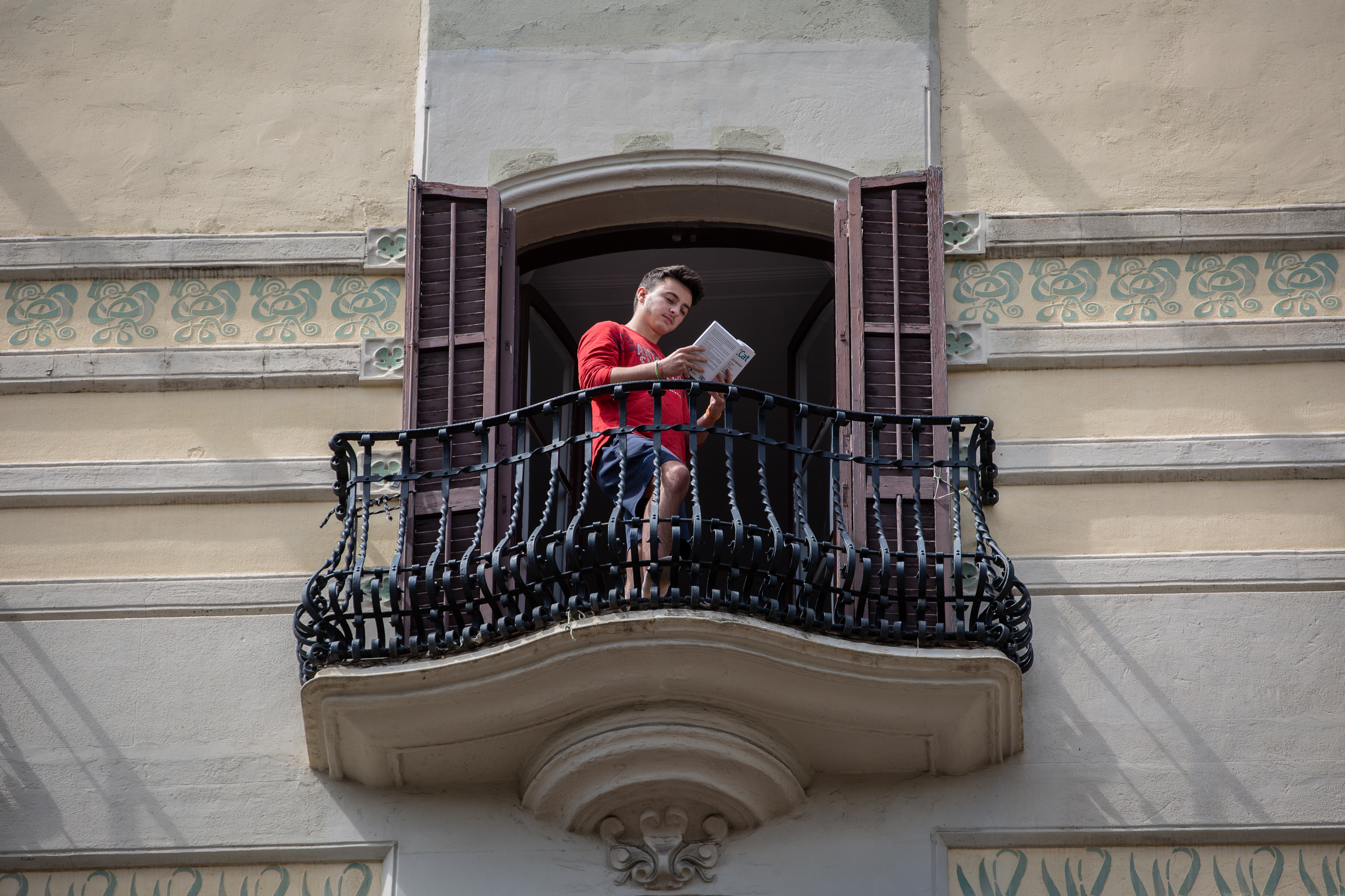 A young man reads a book on the balcony of his house on the occasion of Sant Jordi Day, when it is usual to offer books and roses on April 23, 2020 in Barcelona, Spain.