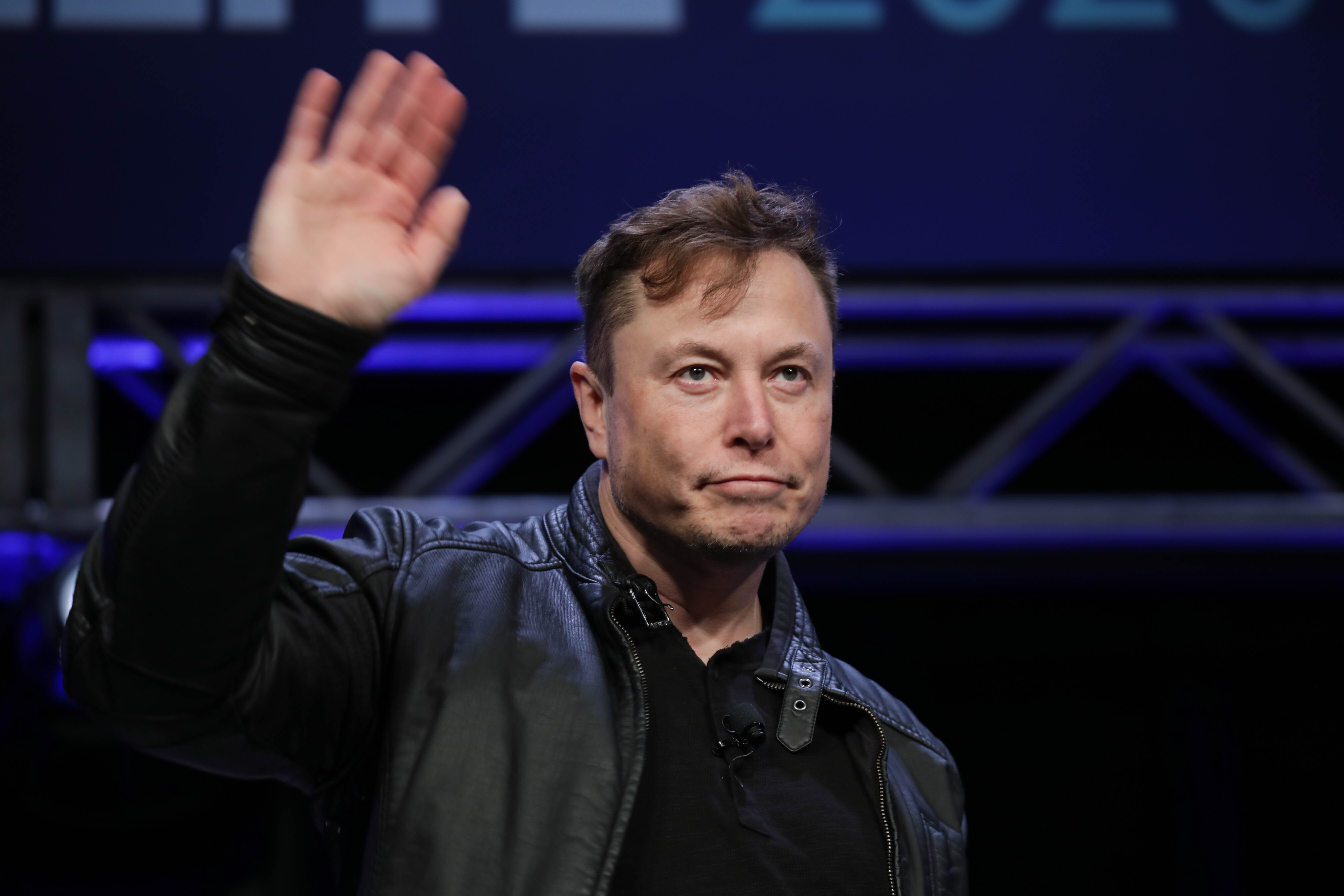 Elon Musk waves from a stage.