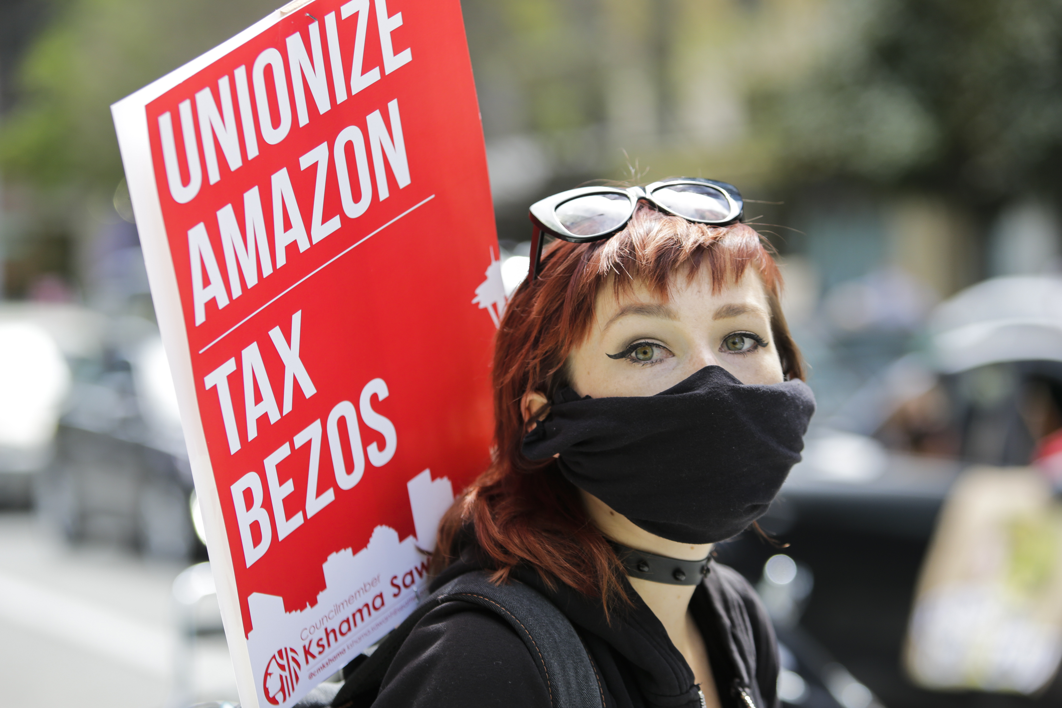 """A protester in a breathing mask carries a sign reading """"Unionize Amazon, tax Bezos."""""""