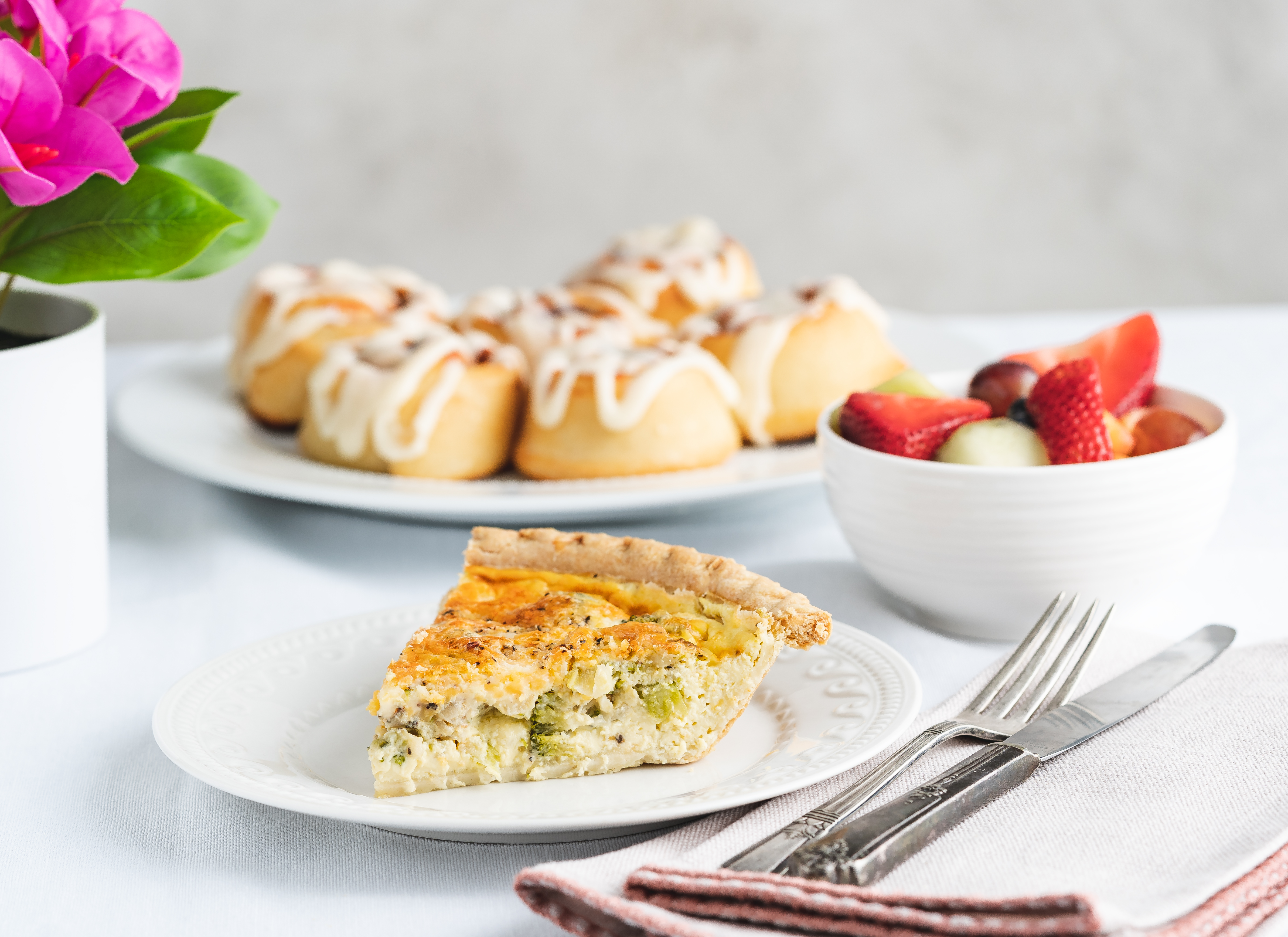 slice of quiche and a platter of cinnamon rolls
