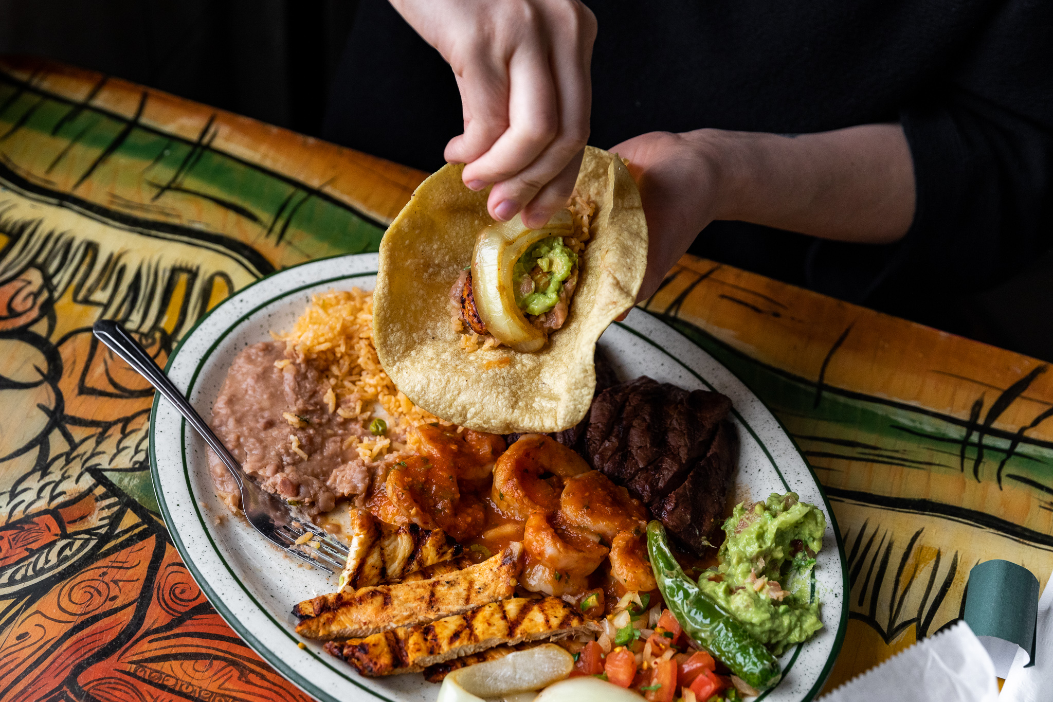 A hand places grilled onion into a tortilla above a plate of grilled chicken, rice, beans, and guacamole.