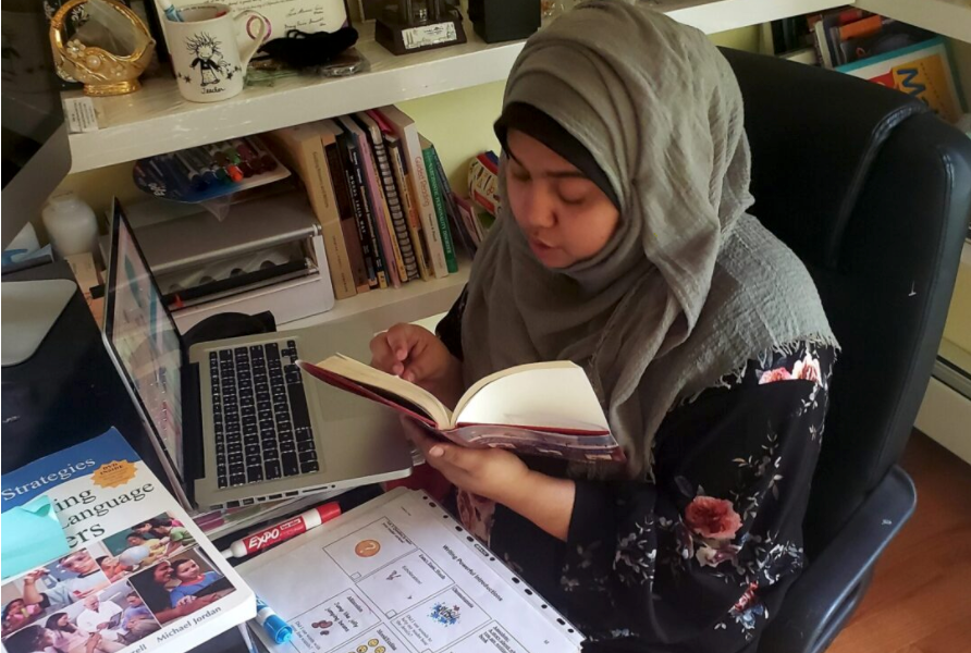 Israt Nali, a third-grade teacher at The Woodside Community School in Queens, virtually reads aloud to her students from her home office. Many of her students are learning English as a new language.