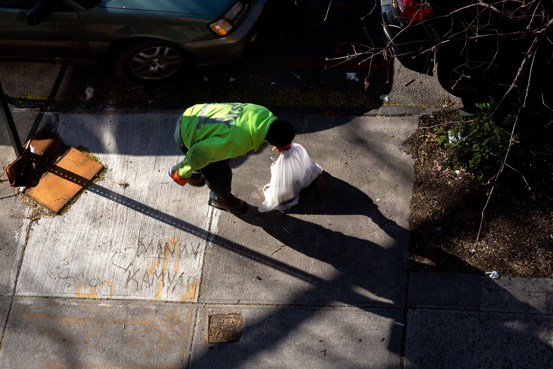 A sanitation worker picks up garbage bags in Bed-Stuy, Brooklyn during the coronavirus outbreak.