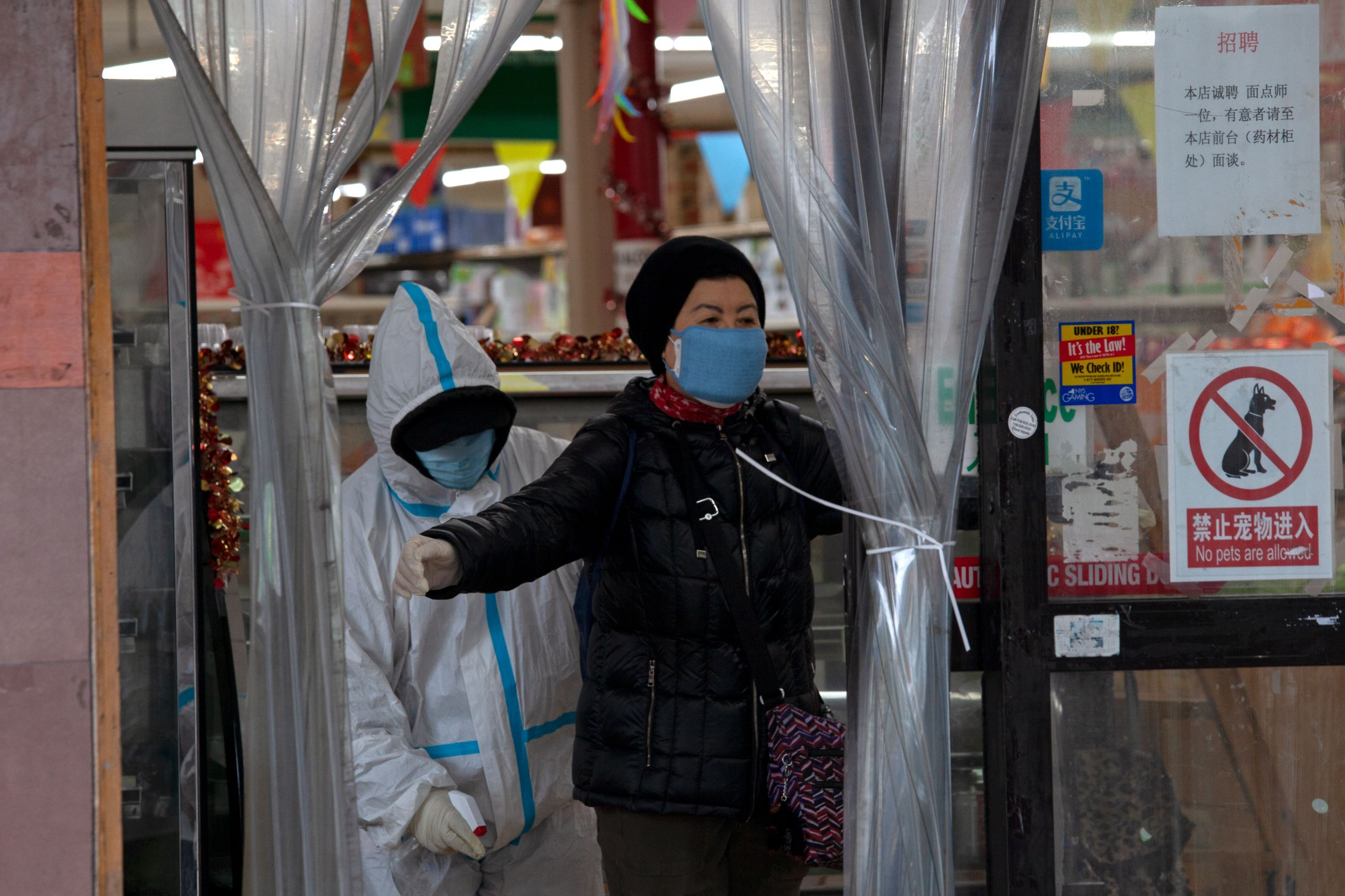 A woman is disinfected after entering a market in Flushing, Queens during the coronavirus outbreak.