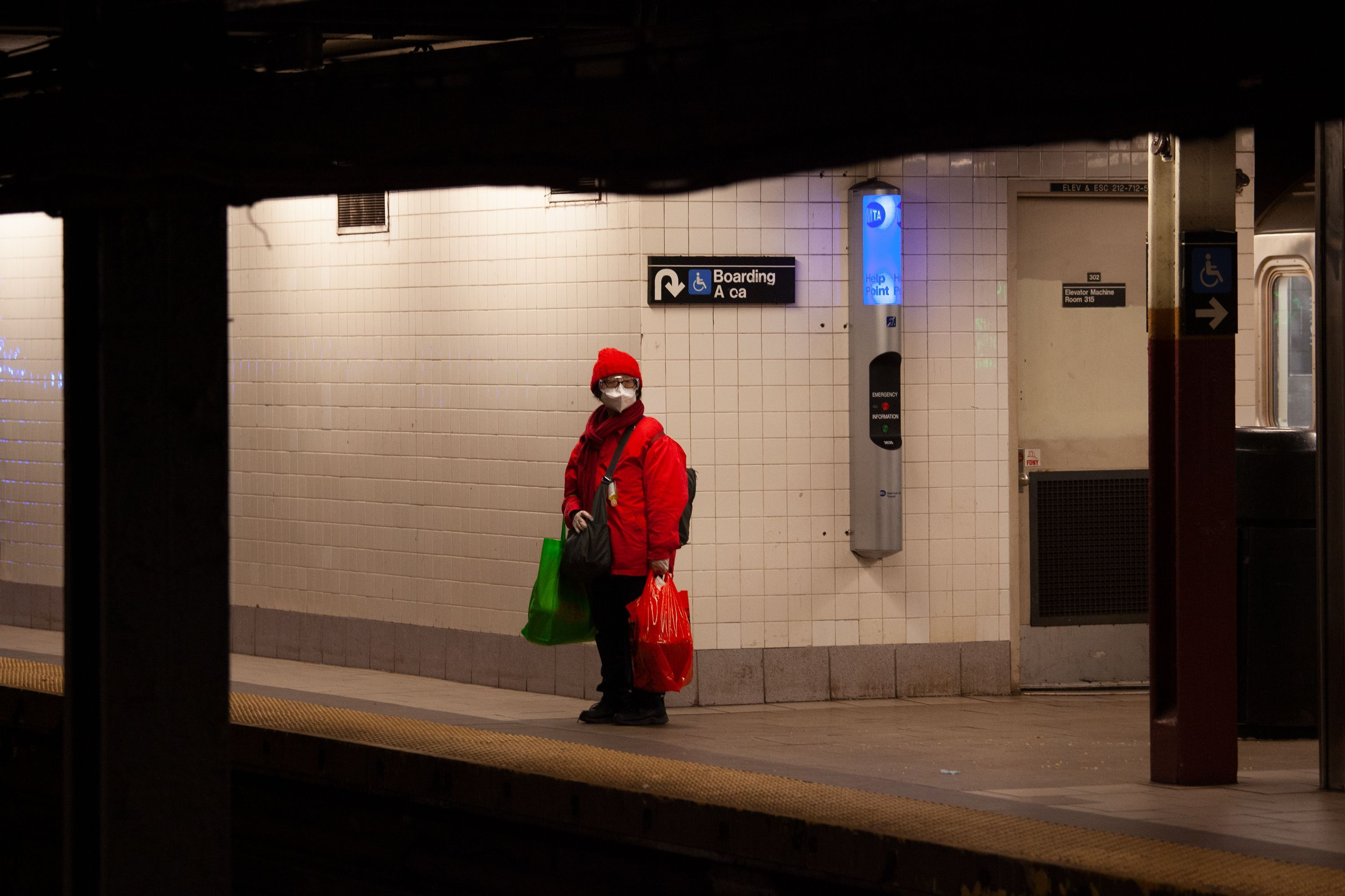 A commuter waits for a downtown 4 or 5 train at the Brooklyn Bridge-City Hall station.
