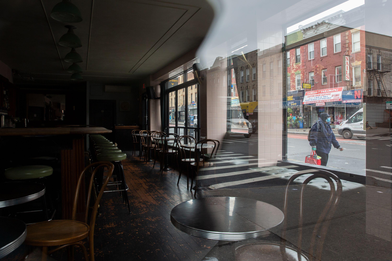 A pedestrian walks by a shuttered bar in Crown Heights, Brooklyn.