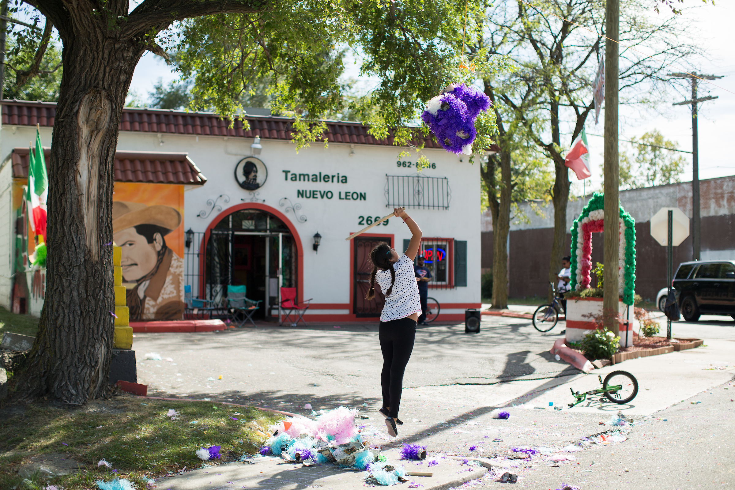 A girl in a white shirt and black jeans is shown mid-air jumping to hit a purple piñata in front of the white and red Tamaleria Nuevo Leon restaurant.